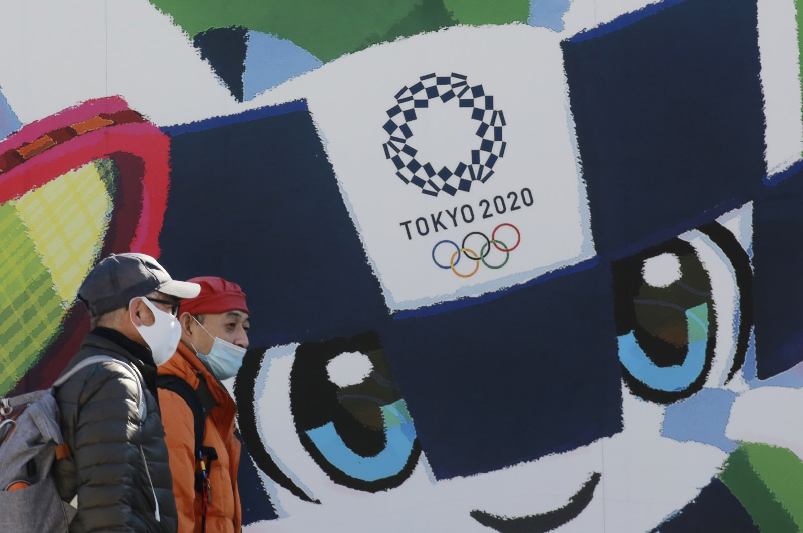 People walk by posters to promote the Tokyo 2020 Olympics planned to start in the summer of 2021, in Tokyo, Jan. 19, 2021. (AP Photo)