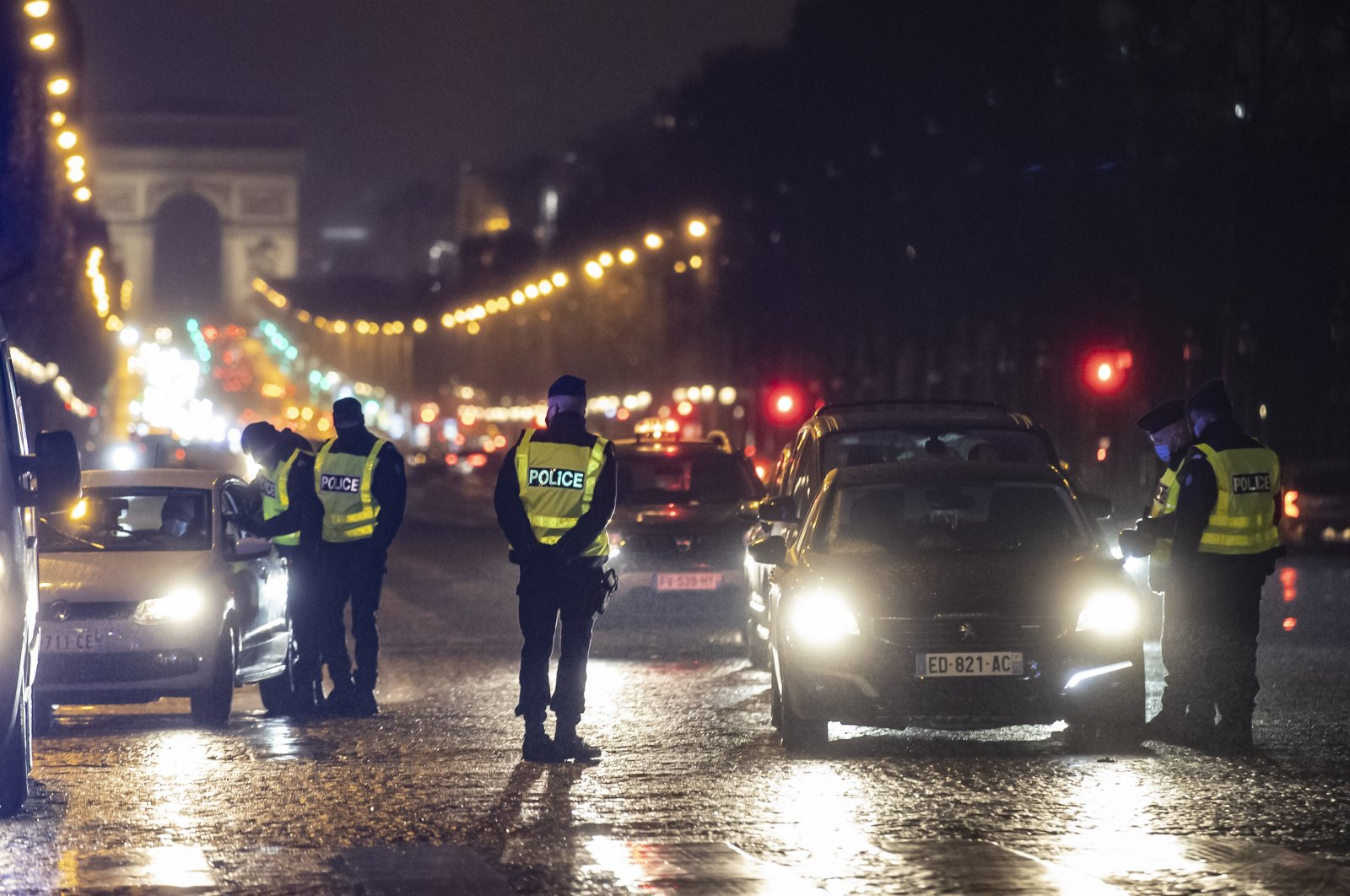 French police officers man a checkpoint on the Champs-Elysees to check drivers' authorizations to be outdoors after the 6 p.m. curfew, in Paris, France, Jan. 16, 2021. (EPA Photo)