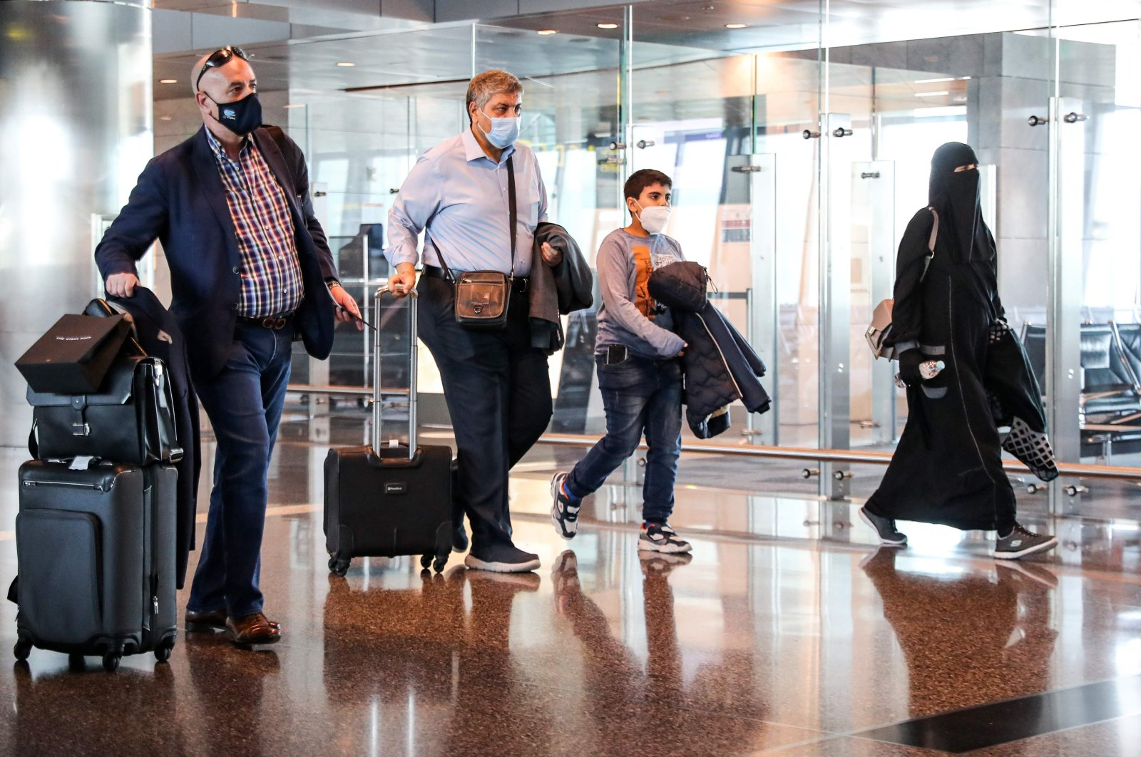Mask-clad travelers walk with their carry-on luggage to board the first Qatar Airways flight bound for Cairo after the resumption of flights between Qatar and Egypt, at Qatar's Hamad International Airport near the capital Doha on Jan. 18, 2021. (AFP Photo)