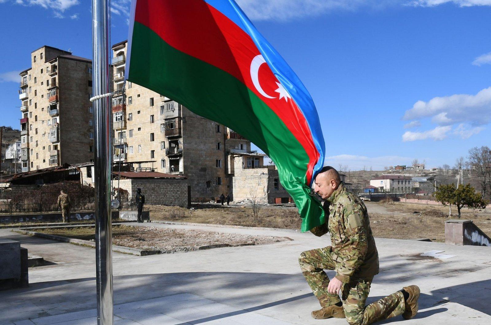 Azerbaijani President Ilham Aliyev kneels in front of the national flag during his visit to the historic town of Shusha in Nagorno-Karabakh, Azerbaijan, Jan. 15, 2021.