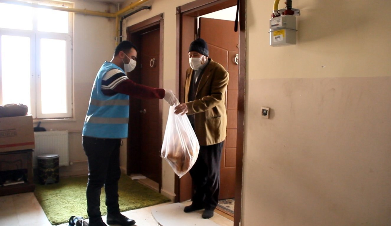 A social support crew member delivers bread to an elderly man in Van, eastern Turkey, Jan. 17, 2021. (DHA PHOTO)