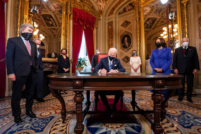U.S. President Joe Biden (C) signs documents as U.S. Vice President Kamala Harris (2nd R) watches after Biden was sworn in as the 46th U.S. president, at the U.S. Capitol, Washington, D.C., U.S., Jan. 20, 2021. (AFP Photo)