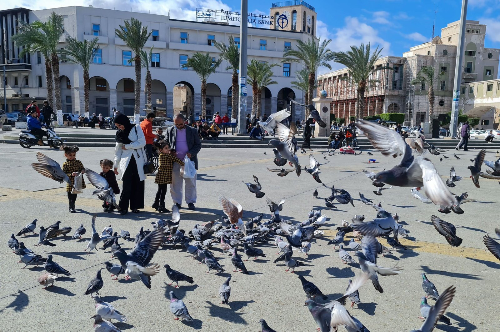 A family feeds pigeons in Martyr's Square in the Libyan capital Tripoli, Jan. 19, 2021. (AFP Photo)