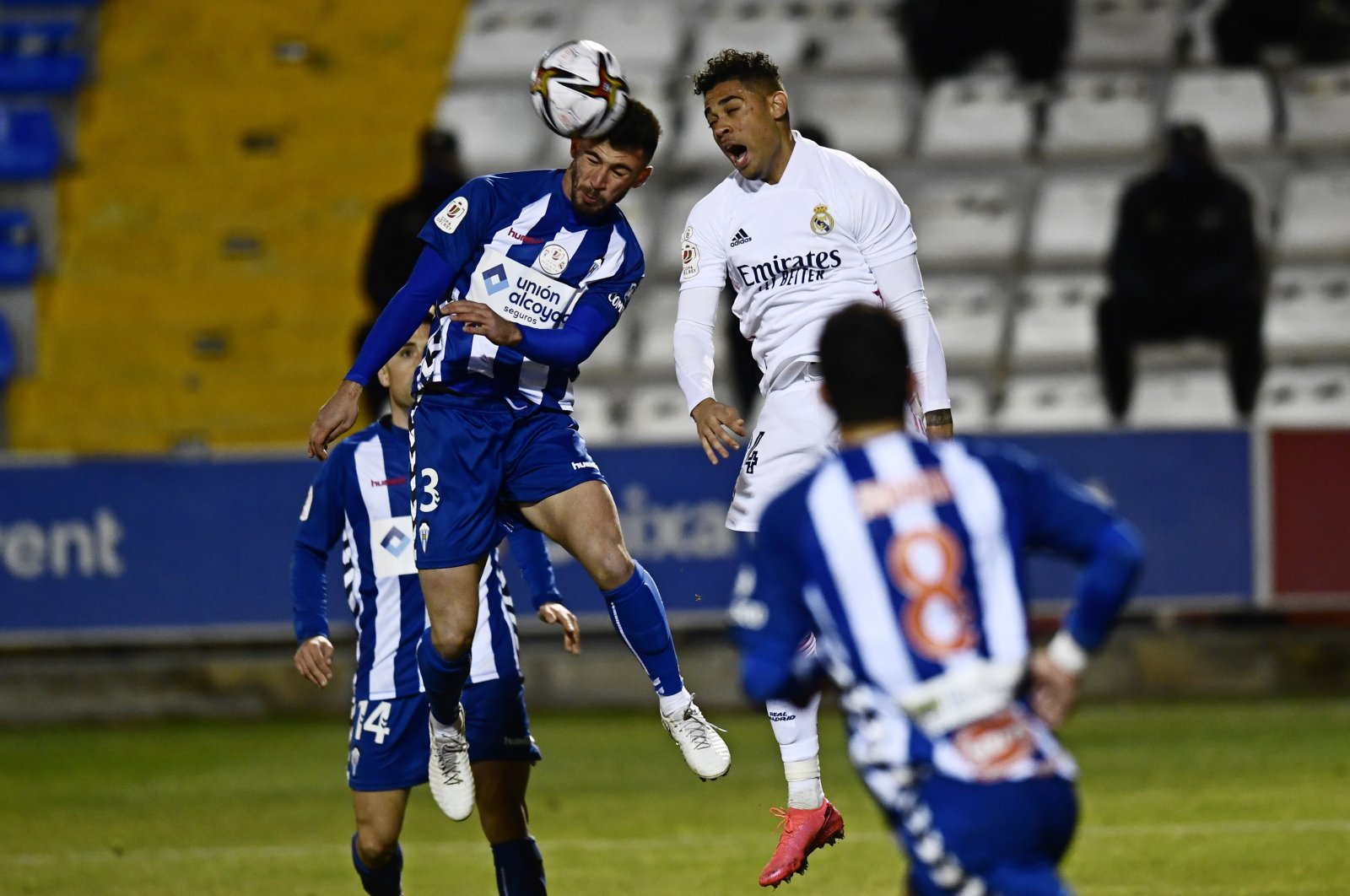 Alcoyano's Jose Solbes (L) and Real Madrid's Mariano Diaz vie for the ball during a Copa del Rey match at the El Collao stadium, Alcoy, Spain, Jan. 20, 2021. (AP Photo)