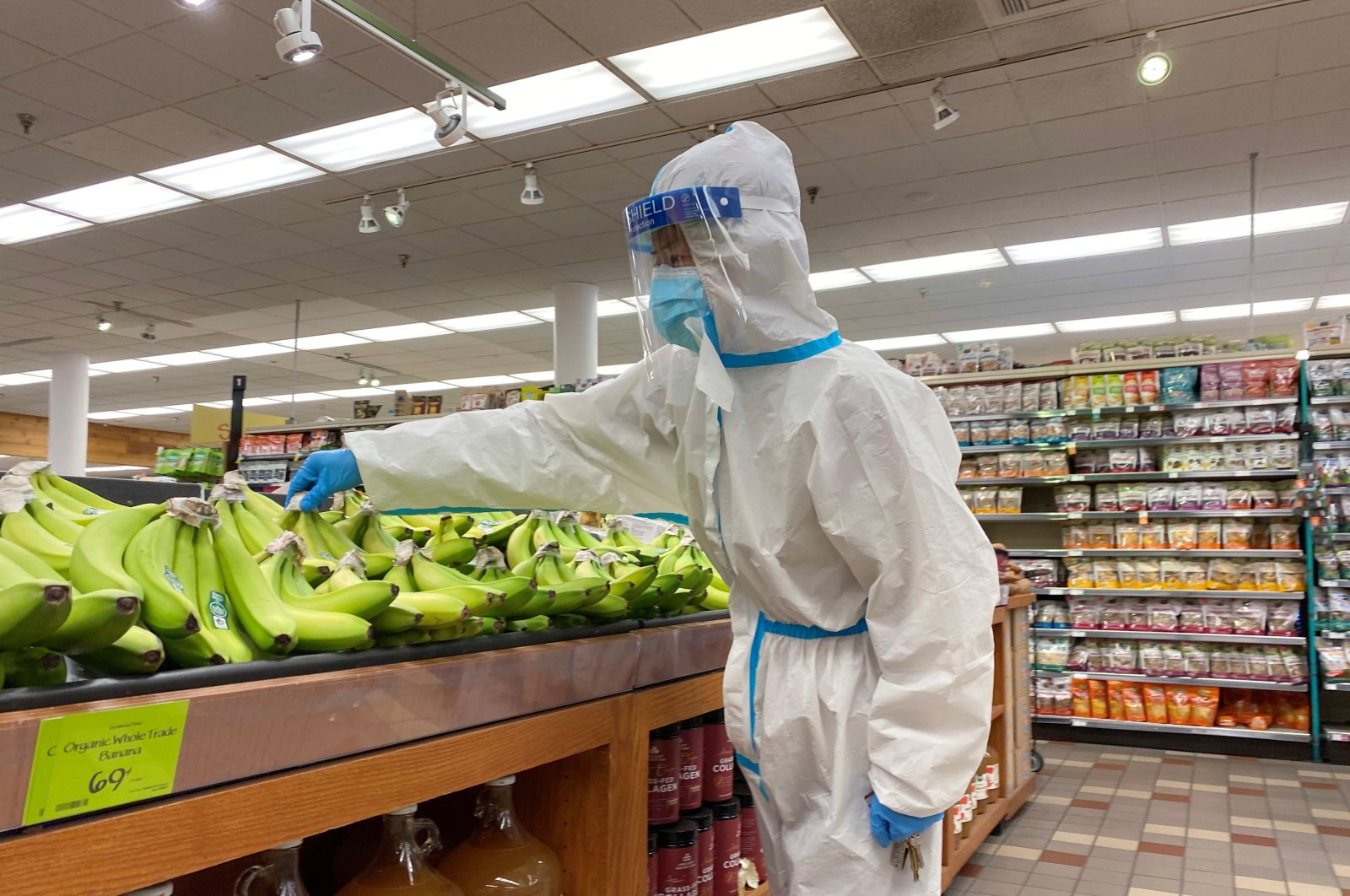 A shopper wearing a personal protective suit, mask and face shield shops for bananas at a Whole Foods Market during the outbreak of the coronavirus disease (COVID-19), in Pasadena, California, Jan. 20, 2021. (Reuters Photo)
