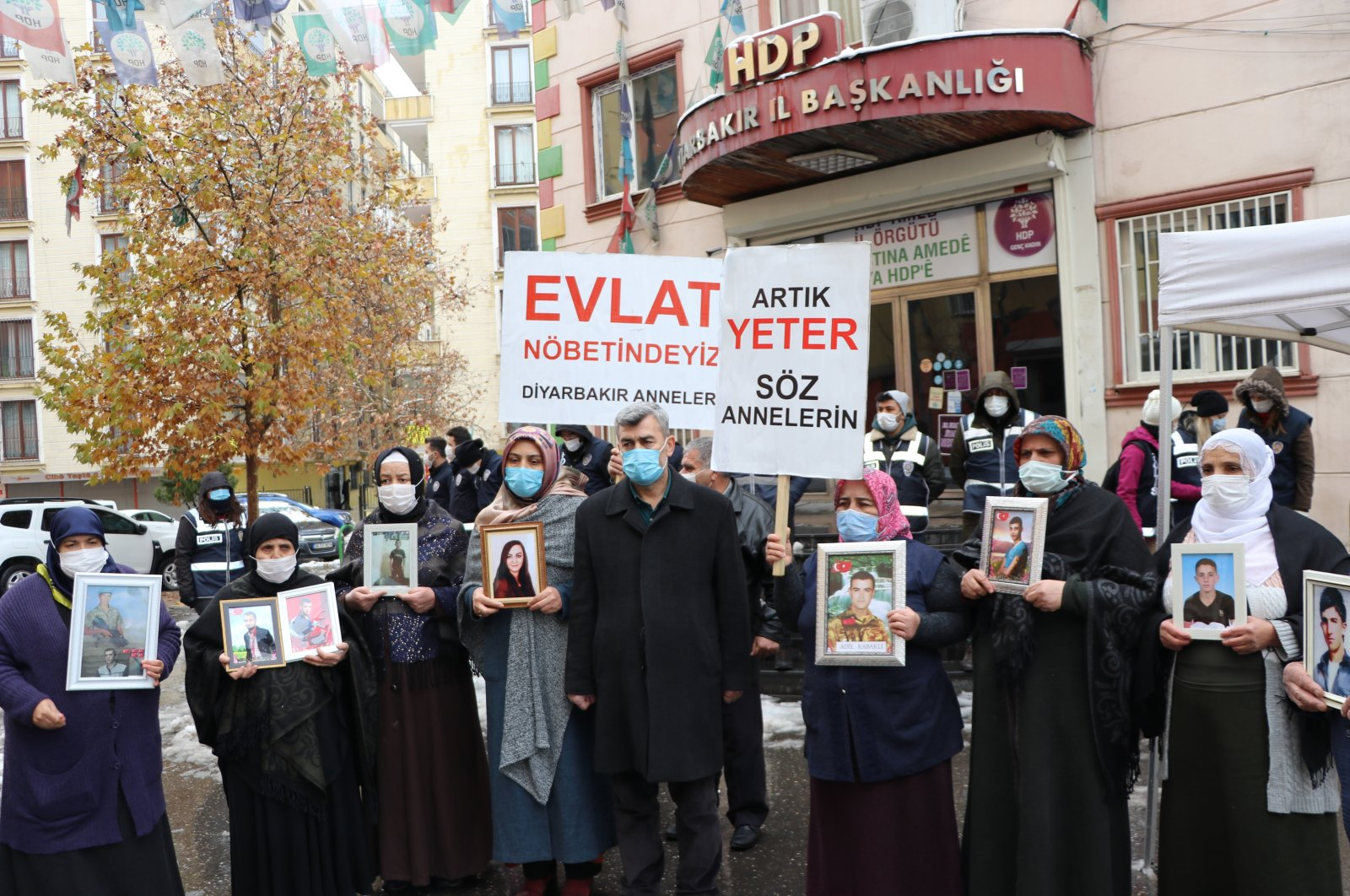 Families holding photos of their children abducted by the PKK terrorist group stand in front of the HDP headquarters in Turkey's Diyarbakır province on Jan. 19, 2021 (AA Photo)