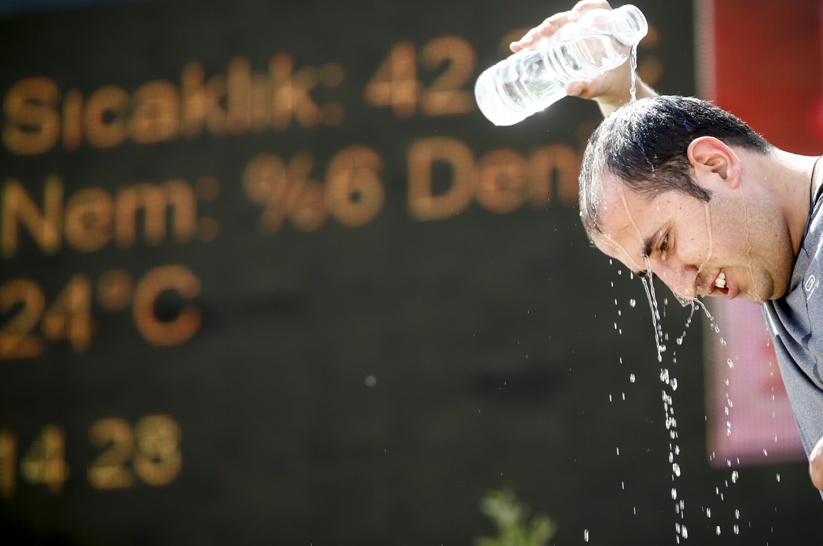 A man pours water on his head in front of a temperature sign reading 42 Celsius degrees, in Antalya, southern Turkey, May 20, 2020. (AA PHOTO)
