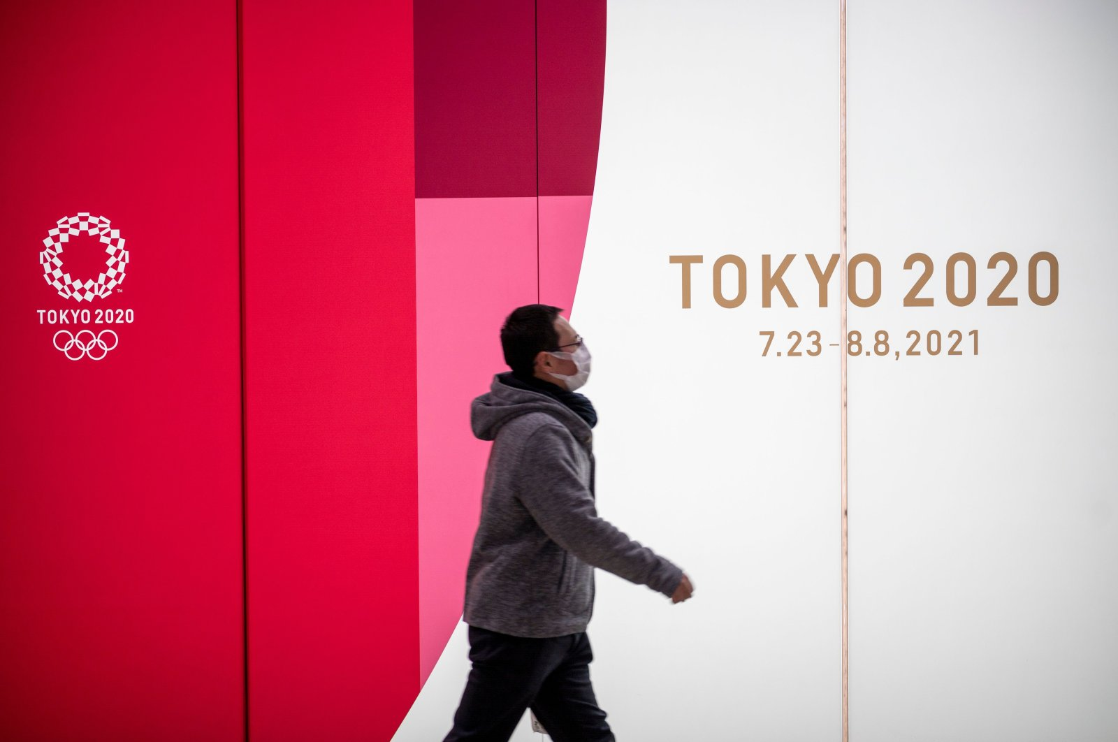 A man walks past Tokyo 2020 Olympic and Paralympic Games advertising in Tokyo's Shinjuku district, Japan, Jan. 20, 2021. (AFP Photo)