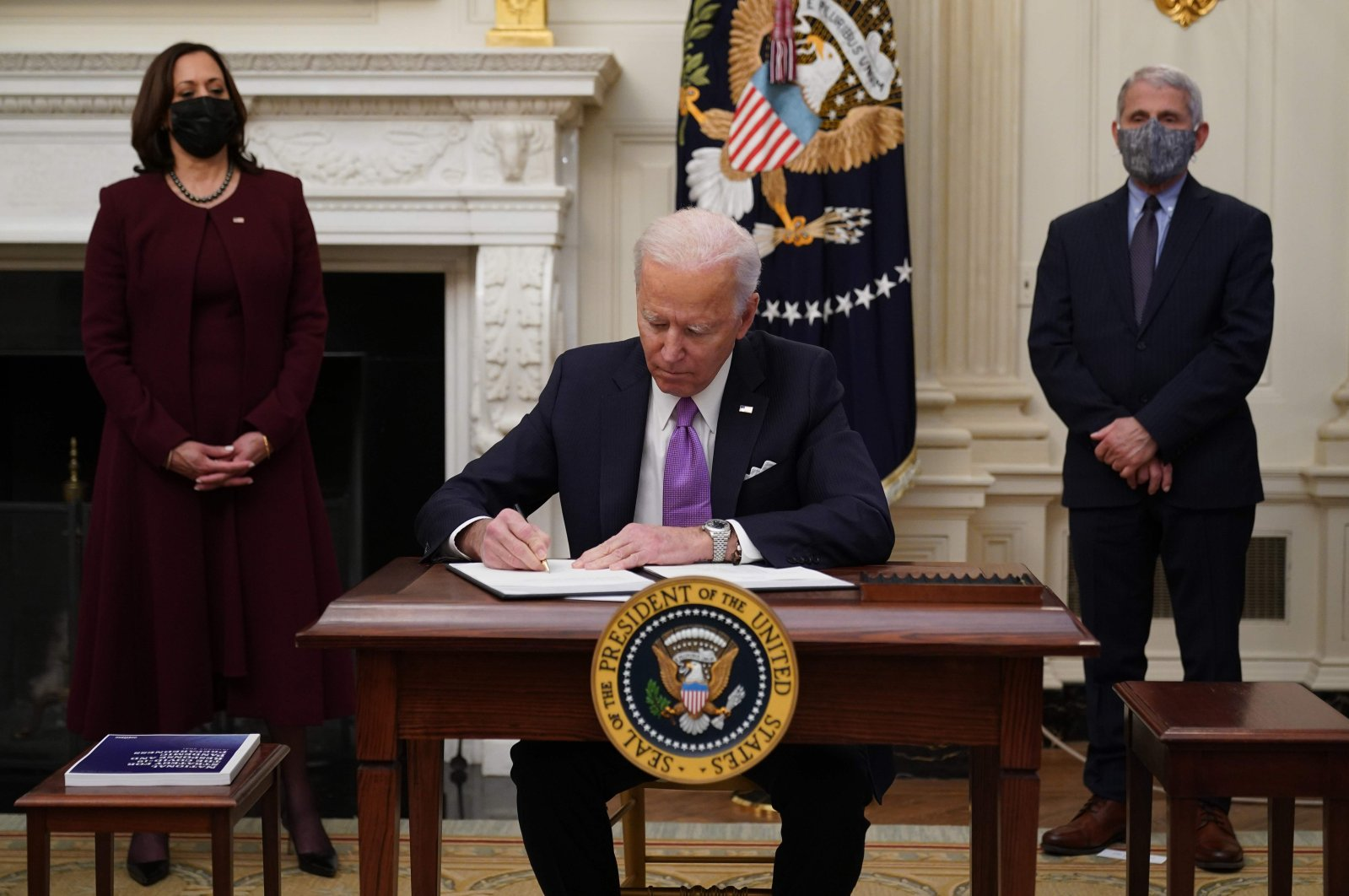 U.S. President Joe Biden (C) signs executive orders as U.S. Vice President Kamala Harris (L) and Director of National Institute of Allergy and Infectious Diseases (NIAID) Anthony Fauci look on in the State Dining Room of the White House, Washington, D.C., U.S., Jan. 21, 2021. (AFP Photo)