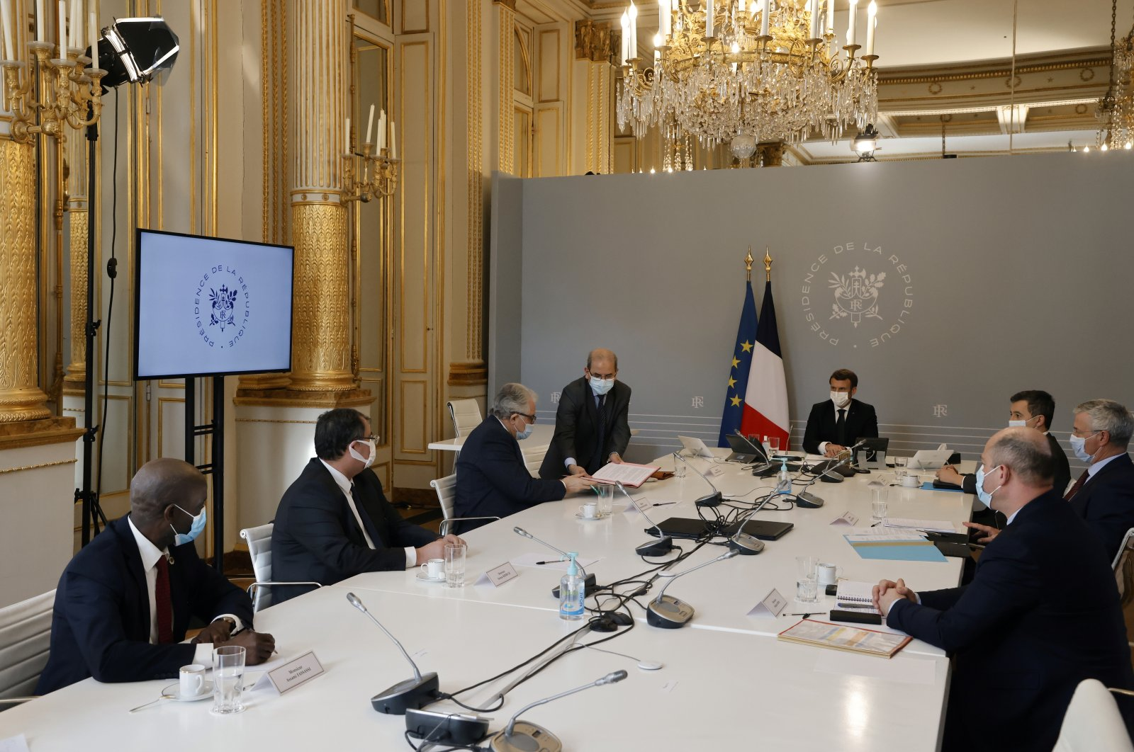 "Mohammed Moussaoui (center L), president of the French Council of the Muslim Faith (CFCM), hands over to Paris' Great Mosque rector Chems-Eddine Hafiz the ""charter of principles"" after signing it next to French President Emmanuel Macron (center R), at the Elysee Palace in Paris, France, Jan. 18, 2021. (Reuters Photo)"