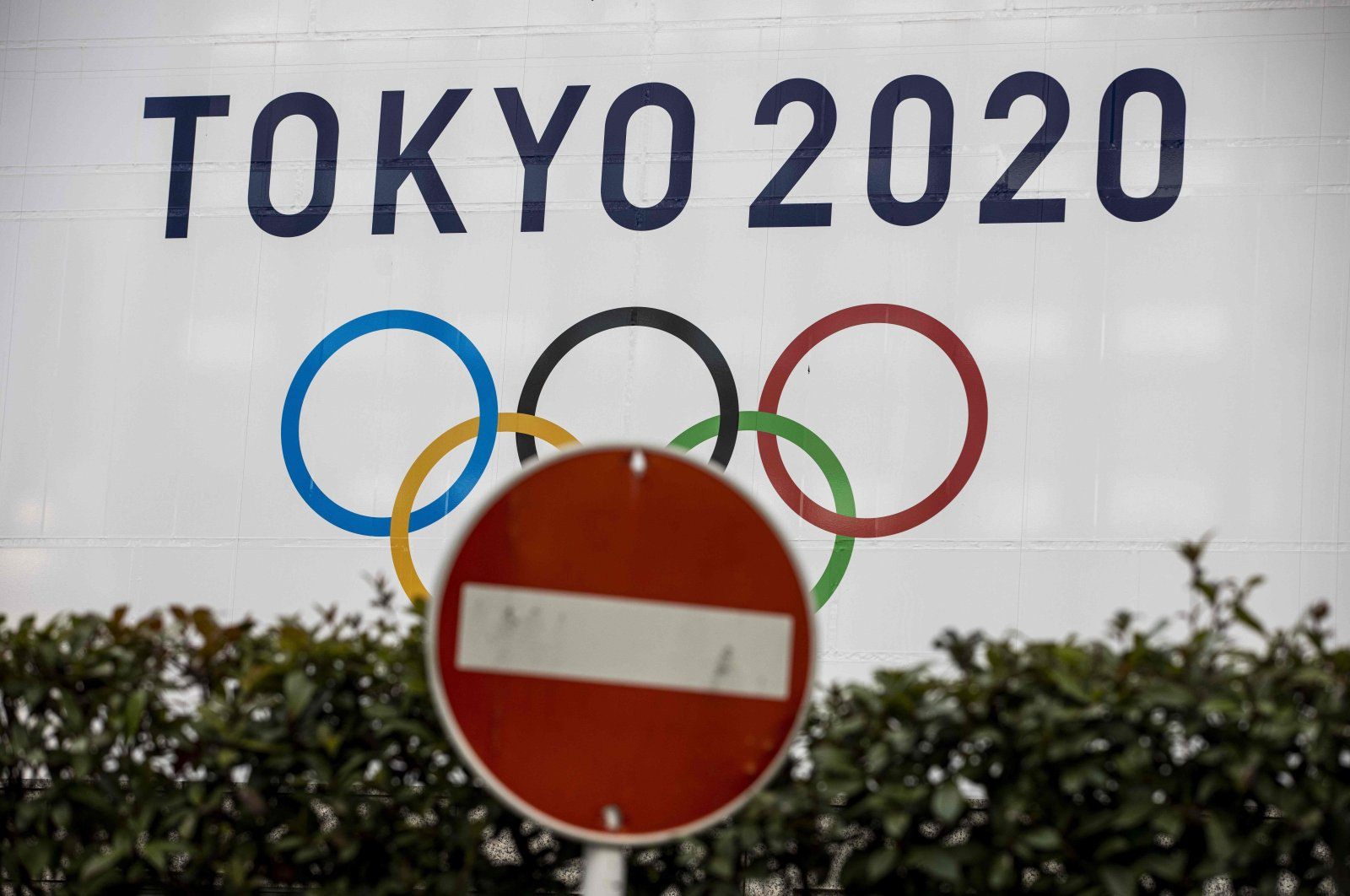 A traffic sign next to an official Tokyo 2020 Olympic Games banner at the Tokyo Metropolitan Government Building, Tokyo, Japan, Jan. 22, 2021. (AFP Photo)