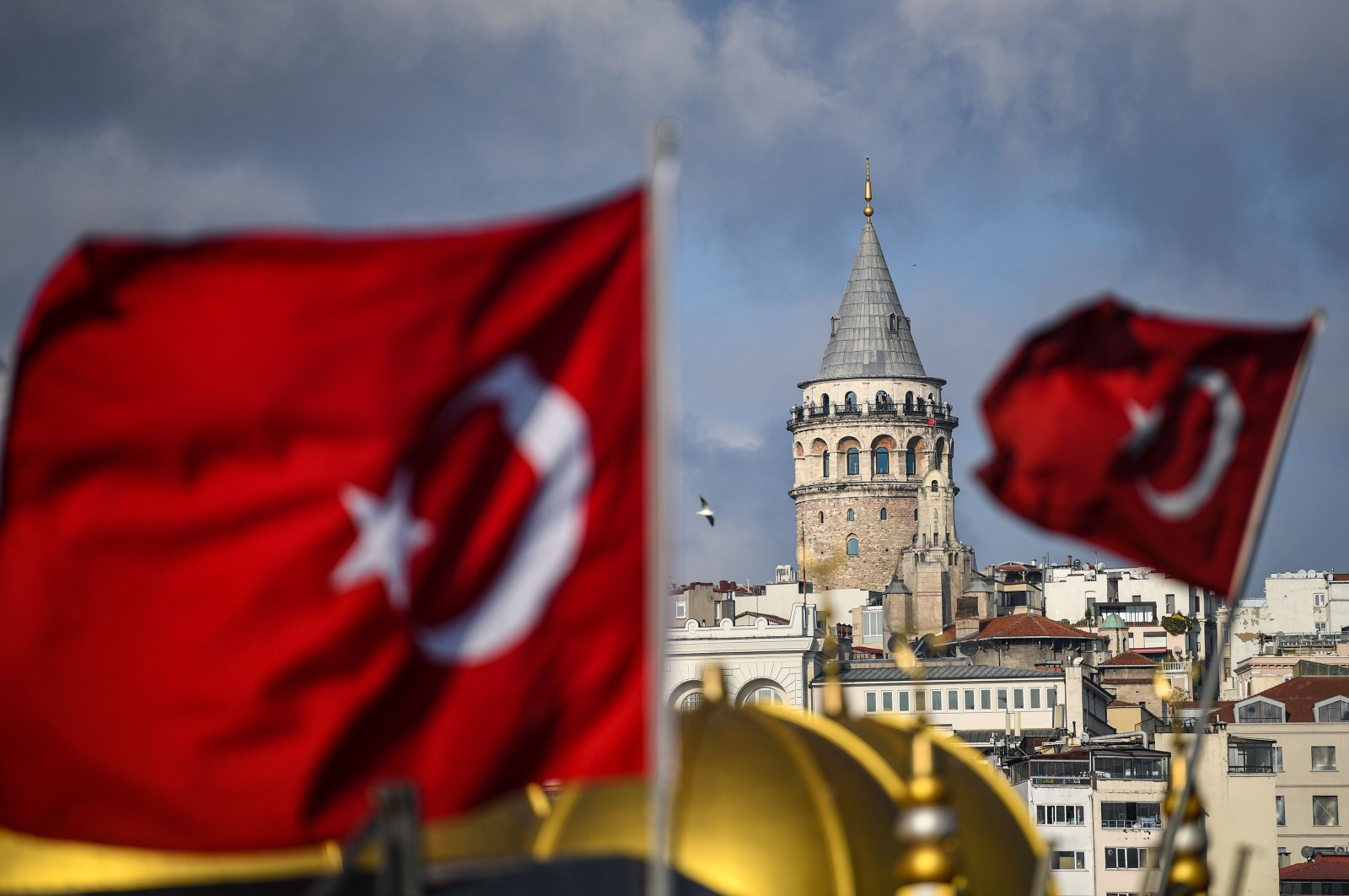 The Galata Tower seen behind Turkish national flags during a curfew against the spread of the coronavirus, Istanbul, Turkey, Dec. 6, 2020. (AFP Photo)