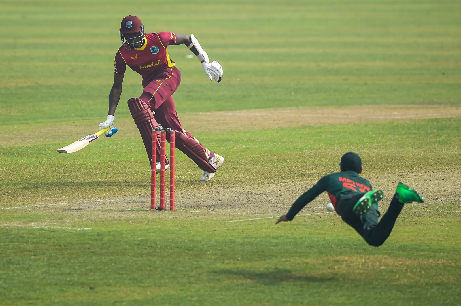 Bangladesh's Mehidy Hasan (R) attempts to run out West Indies' Alzarri Joseph during the second one-day international between Bangladesh and West Indies at the Sher-e-Bangla National Cricket Stadium, Dhaka, Jan. 22, 2021. (AFP Photo)