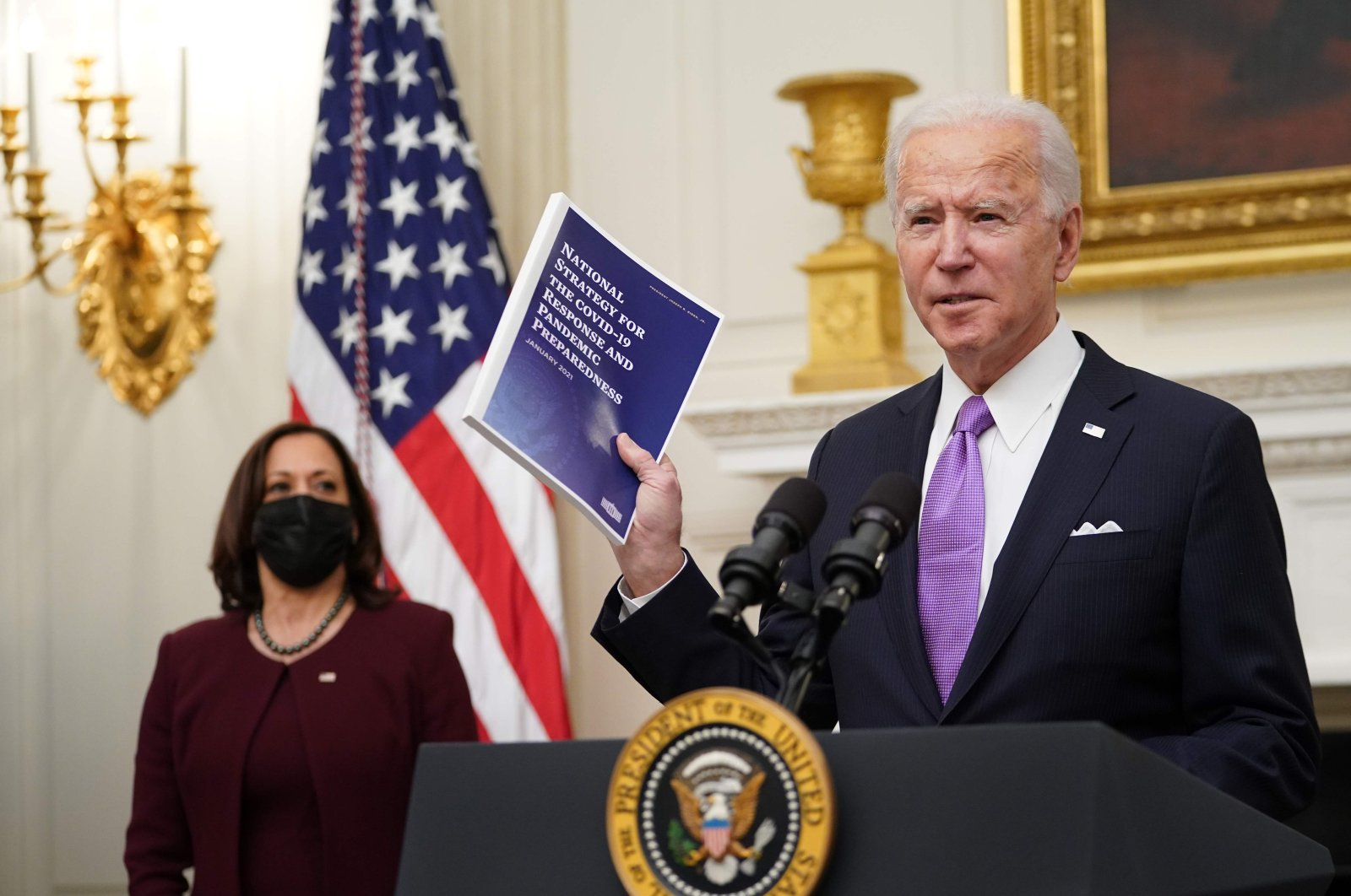 U.S. President Joe Biden speaks about the COVID-19 response as U.S. Vice President Kamala Harris (L) looks on before signing executive orders in the State Dining Room of the White House in Washington, D.C., U.S., Jan. 21, 2021. (AFP Photo)