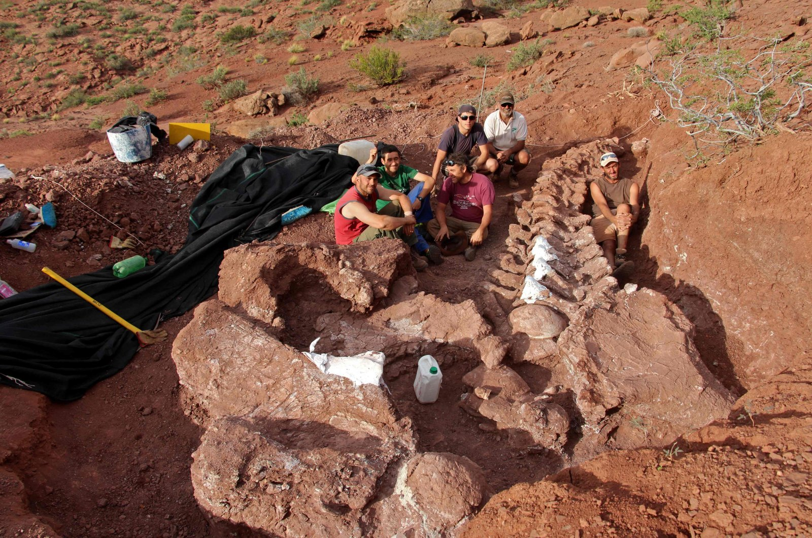 In this photo released by the CTyS-UNLaM Science Outreach Agency, paleontologists sit during an excavation in which 98-million-year-old fossils were found, at the Candeleros Formation in the Neuquen River Valley in southwest Argentina, Jan. 20, 2021. (Jose Luis Carballido/CTyS-UNLaM via AFP)