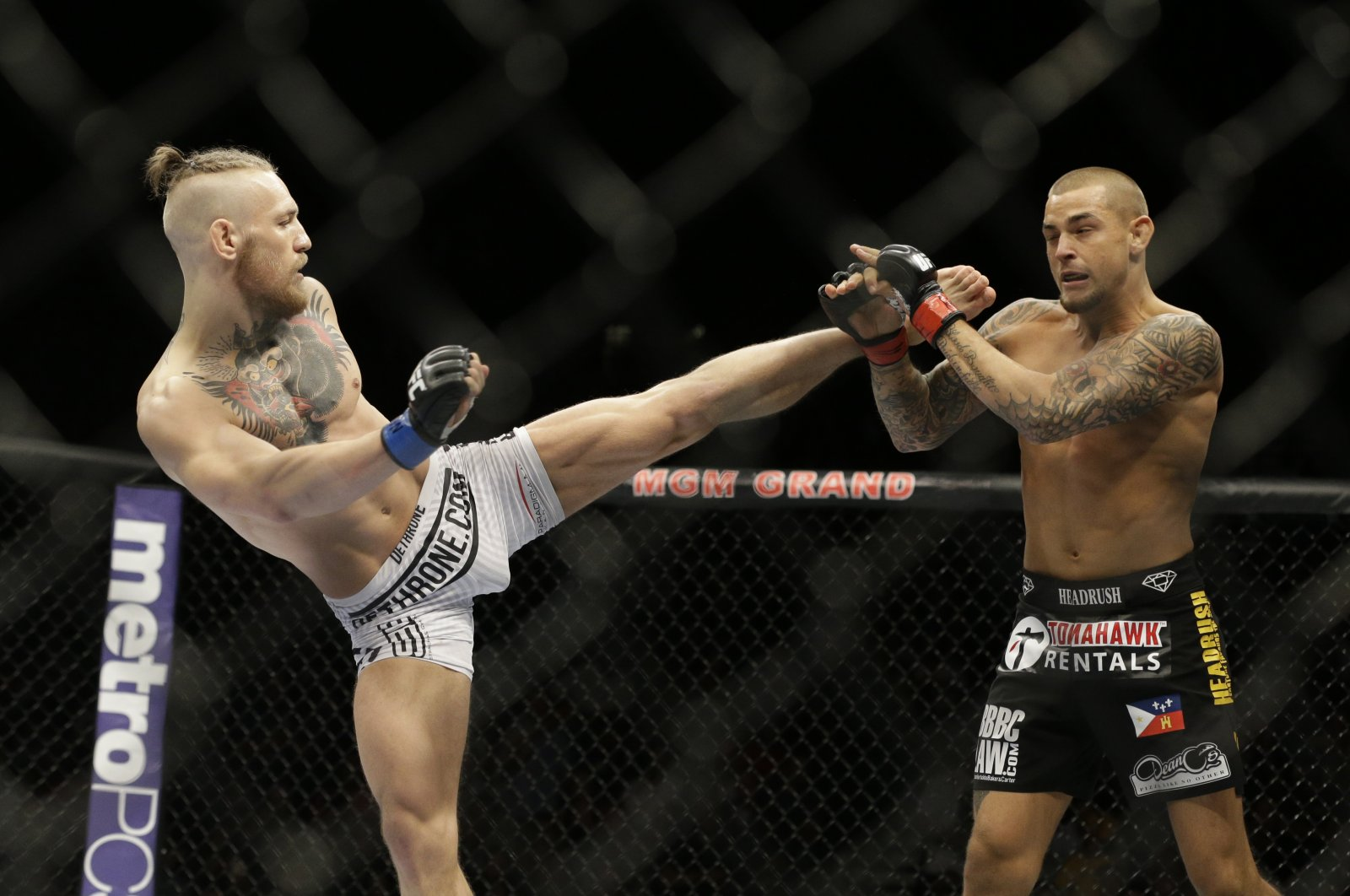 Conor McGregor (L) kicks Dustin Poirier during their mixed martial arts bout in Las Vegas, Nevada, Sept. 27, 2014.  McGregor returns from a year-long layoff for a rematch against Poirier in the promotions' first pay-per-view of the year, at UFC 257 on Jan. 24 in Abu Dhabi. (AP Photo)