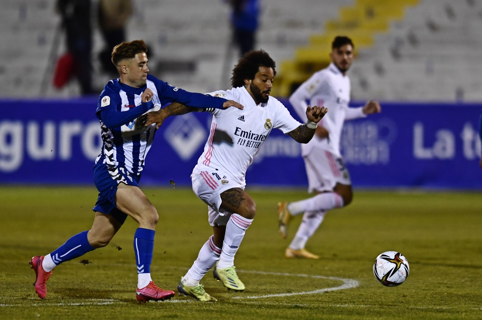 Real Madrid's Marcelo, center holds off Alcoyano's Alberto Rubio during a Spanish Copa del Rey round of 32 soccer match between Alcoyano and Real Madrid at the El Collao stadium in Alcoy, Spain, Jan. 20, 2021. (AP Photo)