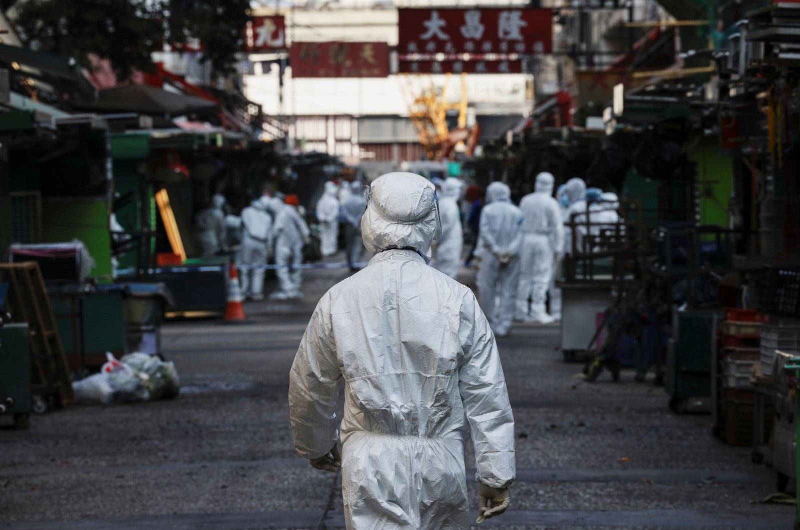 Health workers wear protective gear inside a locked down portion of the Jordan residential area to contain a new outbreak of COVID-19, in Hong Kong, China on Jan. 23, 2021. (Reuters Photo)