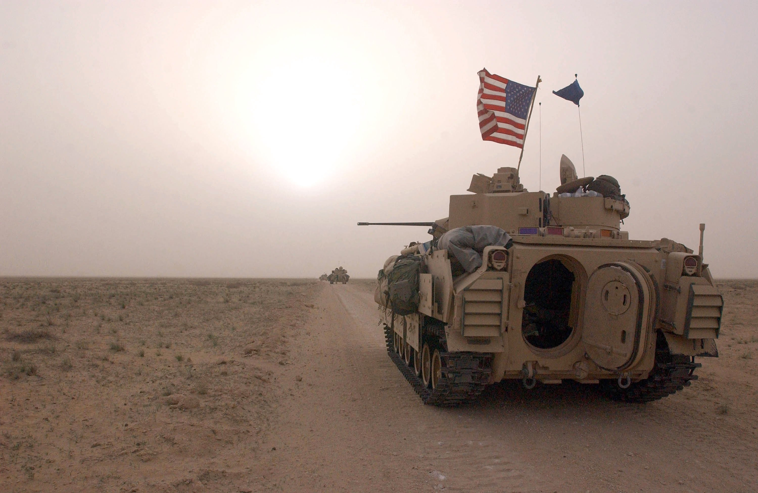 U.S. military vehicles take up a position along a road inside the demilitarized zone between Kuwait and Iraq, March 19, 2003. (Photo by Getty Images)