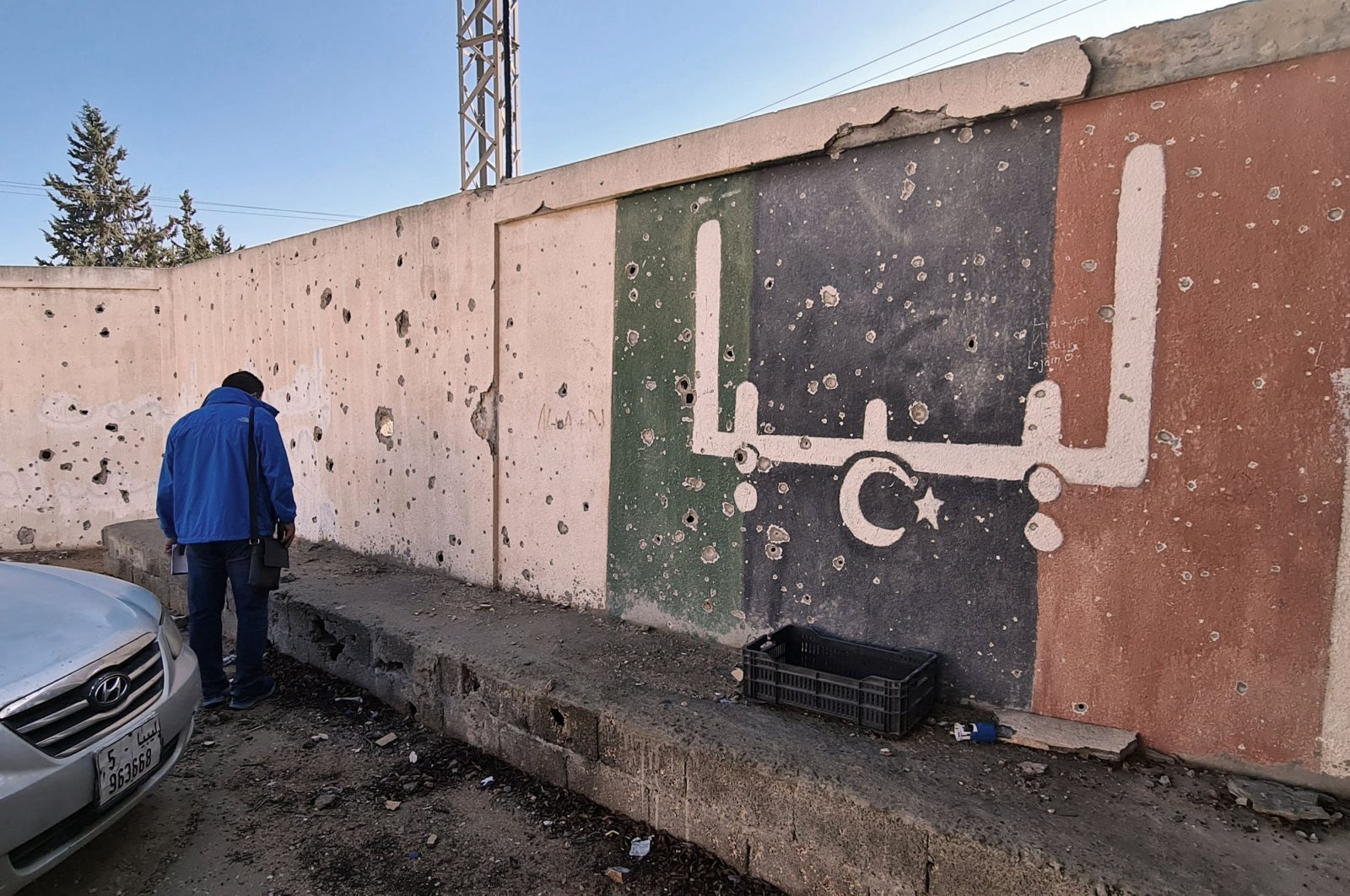 """A Libyan stands in front of a school, which was damaged during fighting between rival factions, in the capital Tripoli's suburb of Ain Zara, Nov. 19, 2020. The writing on the wall reads """"Libya"""" in Arabic. (AFP Photo)"""