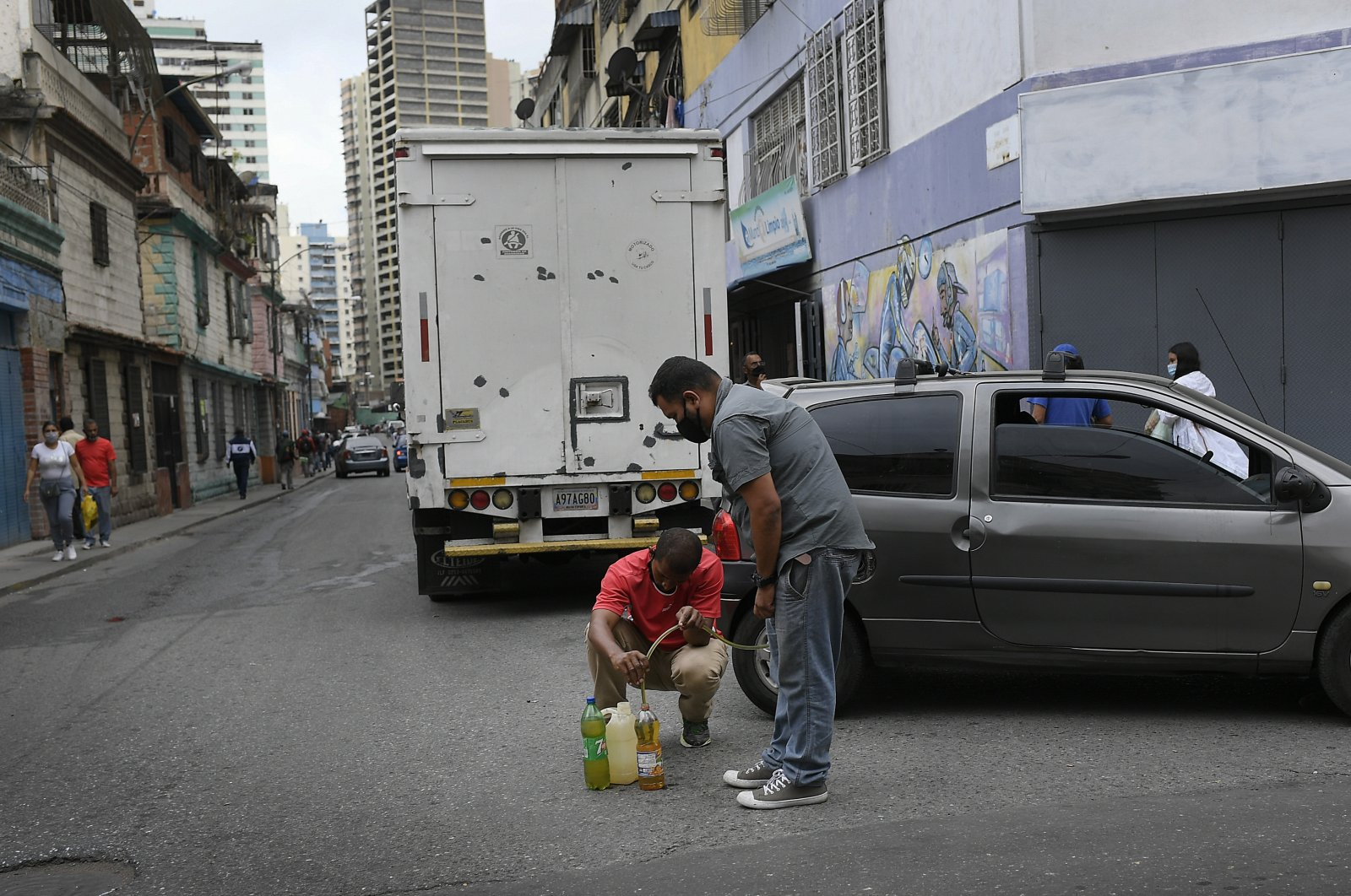 Men siphon gasoline from a car to store so they can return to the gas station to fill up again, in the San Juan neighborhood of Caracas, Venezuela, Jan. 19, 2021. (AP Photo)