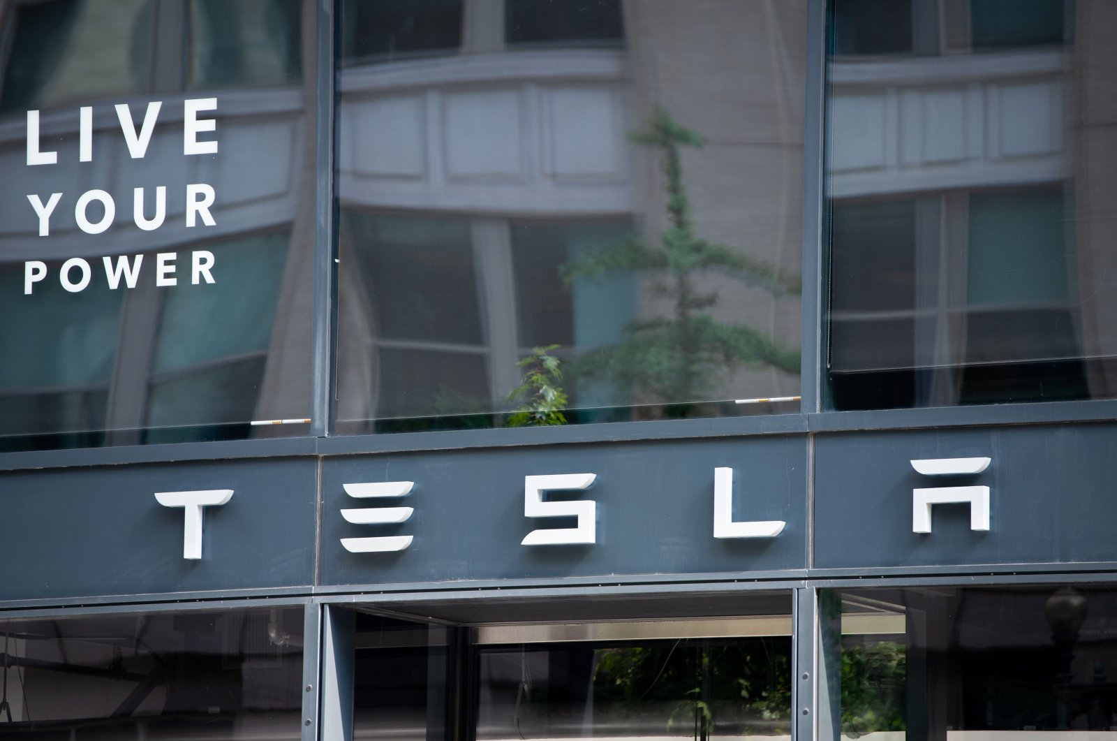 In this file photo, the Tesla logo is seen outside of their showroom in Washington, D.C., on Aug. 8, 2018. (AFP Photo)