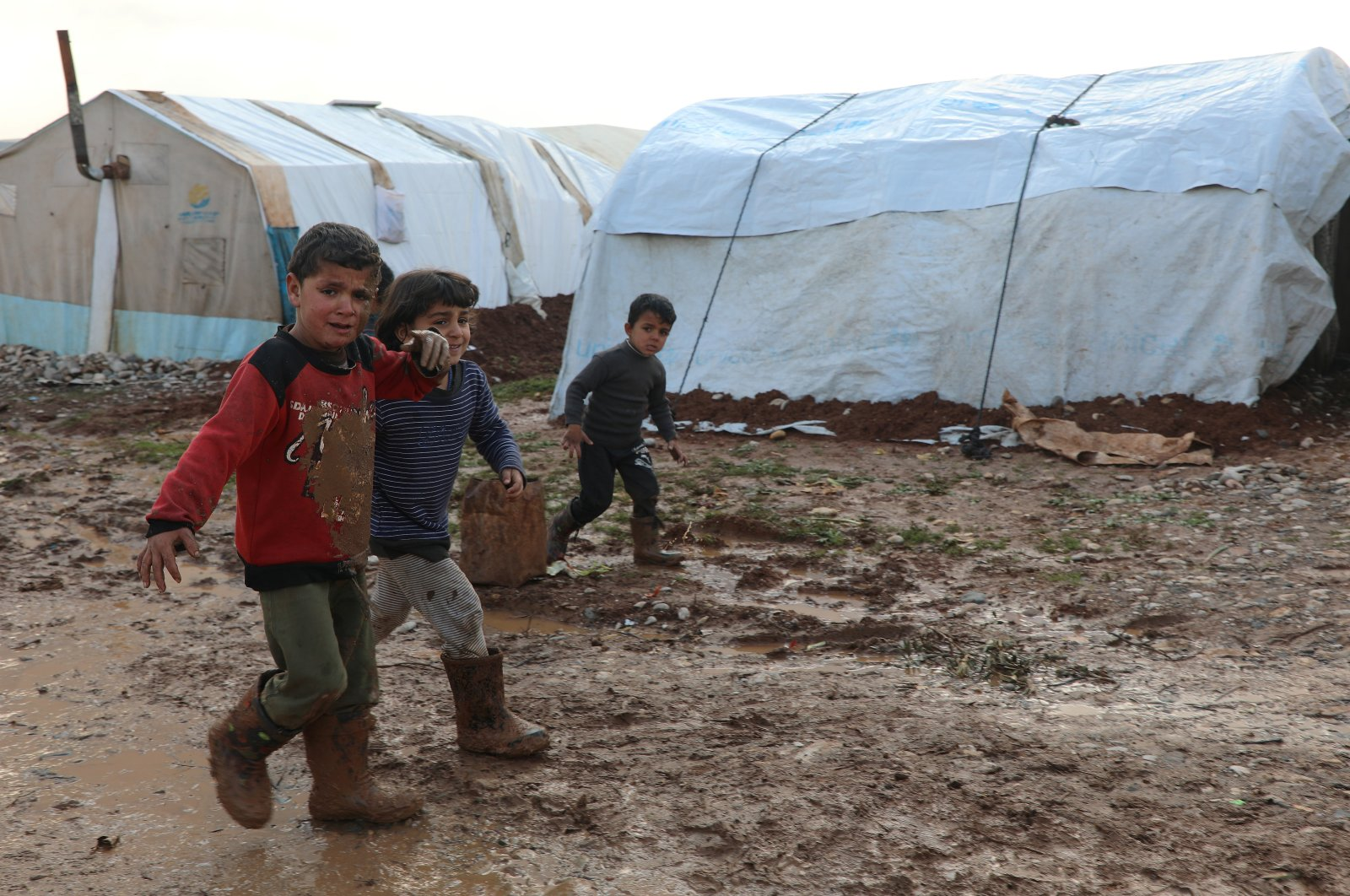 Internally displaced Syrian children walk in a mud near tents, in Northern Aleppo countryside, Syria, Jan. 20, 2021. (Reuters Photo)