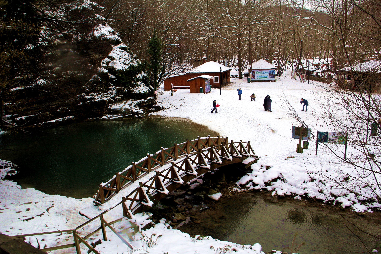 Families enjoy the snow near a pond at Erfelek Tatlıca Waterfalls Natural Park, Sinop, northern Turkey, Jan. 22, 2021. (AA Photo)