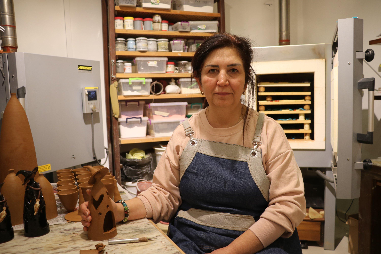 Esen Hüsmenoğlu at her workshop with different pottery works on display around her, in Çanakkale, northwestern Turkey, Jan. 23, 2021. (AA Photo)