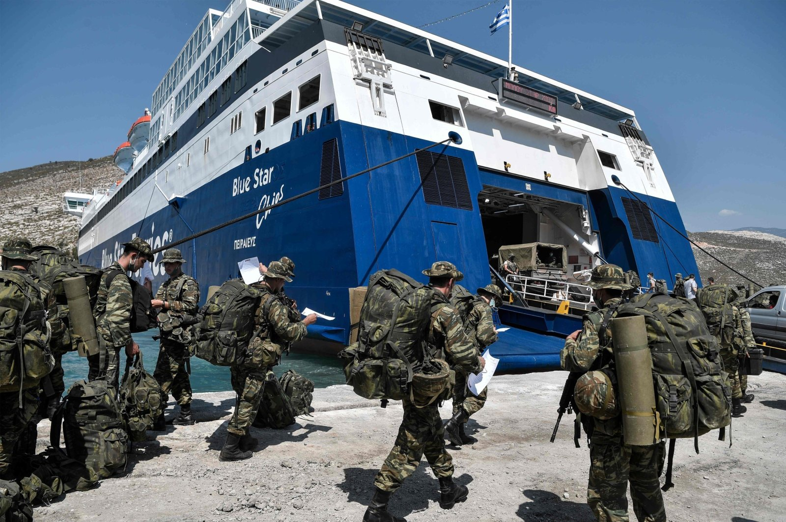 Greek soldiers prepare to board a ferry at the port of the tiny Greek island of Kastellorizo (Megisti-Meis), the southeasternmost inhabited Greek island in the Dodecanese, situated 2 kilometers (1.2 miles) off the south coast of Turkey, in Kastellorizo, Greece, Aug. 31, 2020. (AFP Photo)