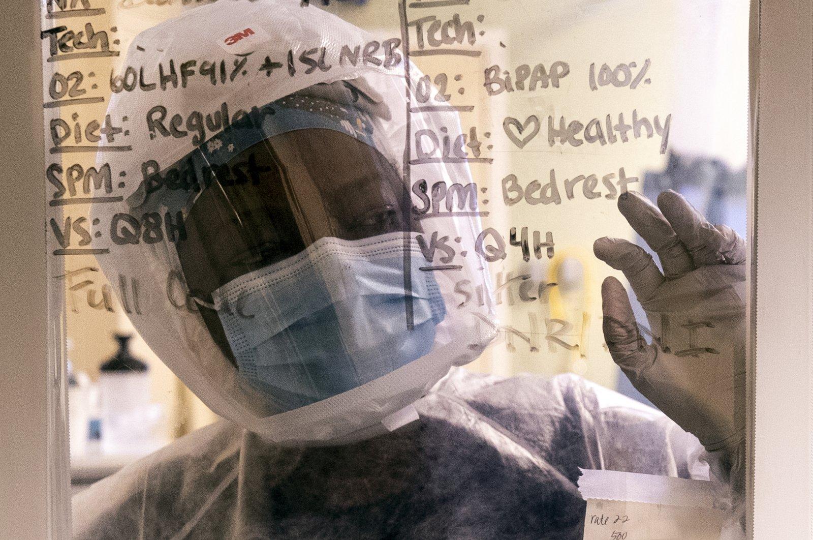 Nurse Ann Lawani looks through the window of a COVID-19 patient's room in the ICU, San Diego, California, U.S., Jan. 20, 2021. (EPA-EFE Photo)