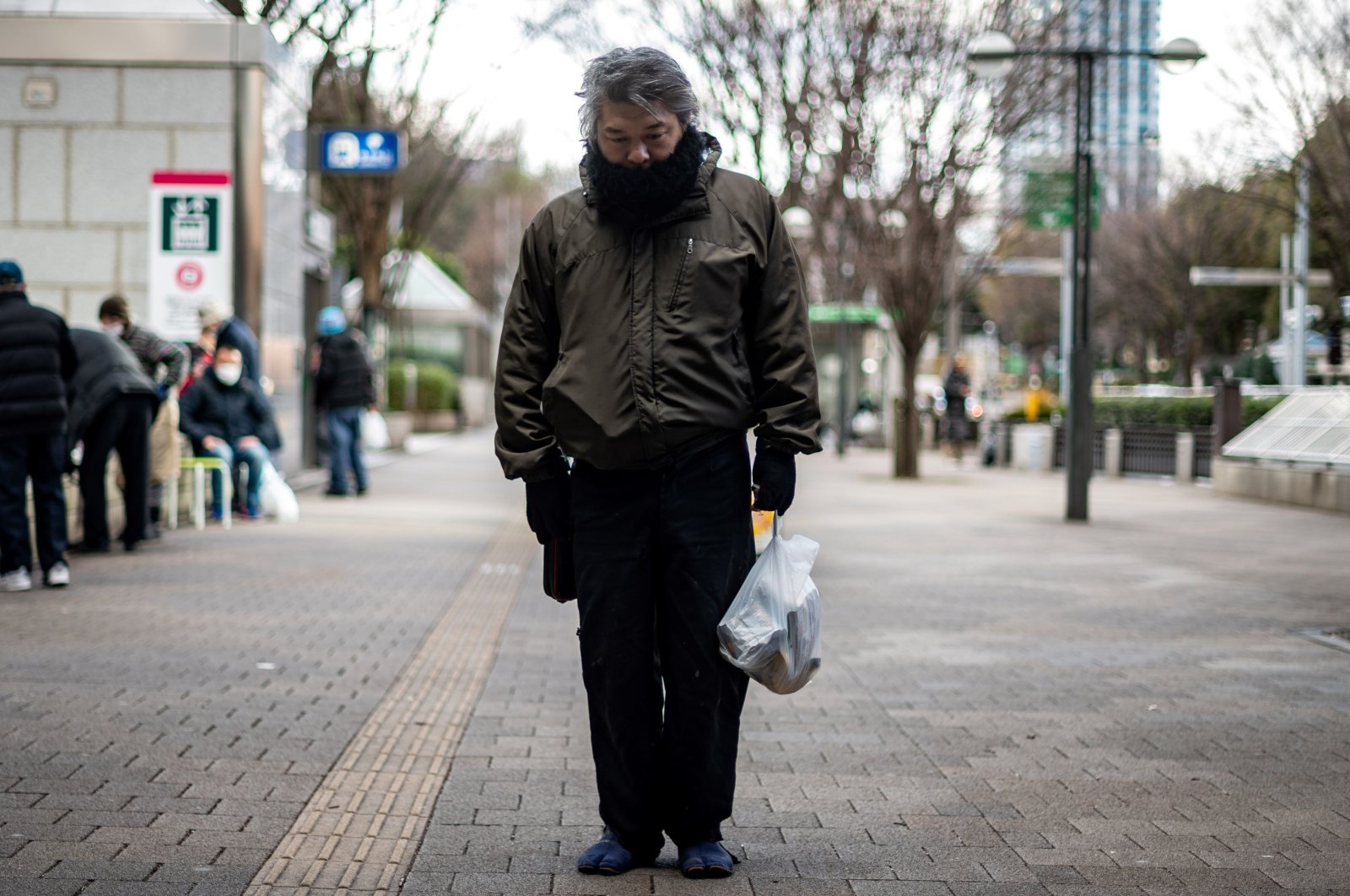 "A man who identified himself as ""Yuichiro"" holds a bag of food distributed by nonprofit organization Moyai Support Centre for Independent Living, in the Shinjuku district of Tokyo, Japan, Jan. 9, 2021. (AFP Photo)"