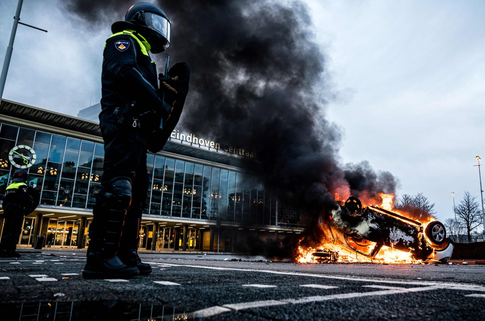 A car is set on fire in front of the train station after a rally by several hundreds of people against the coronavirus policies, in Eindhoven, the Netherlands, Jan. 24, 2021. (AFP Photo)