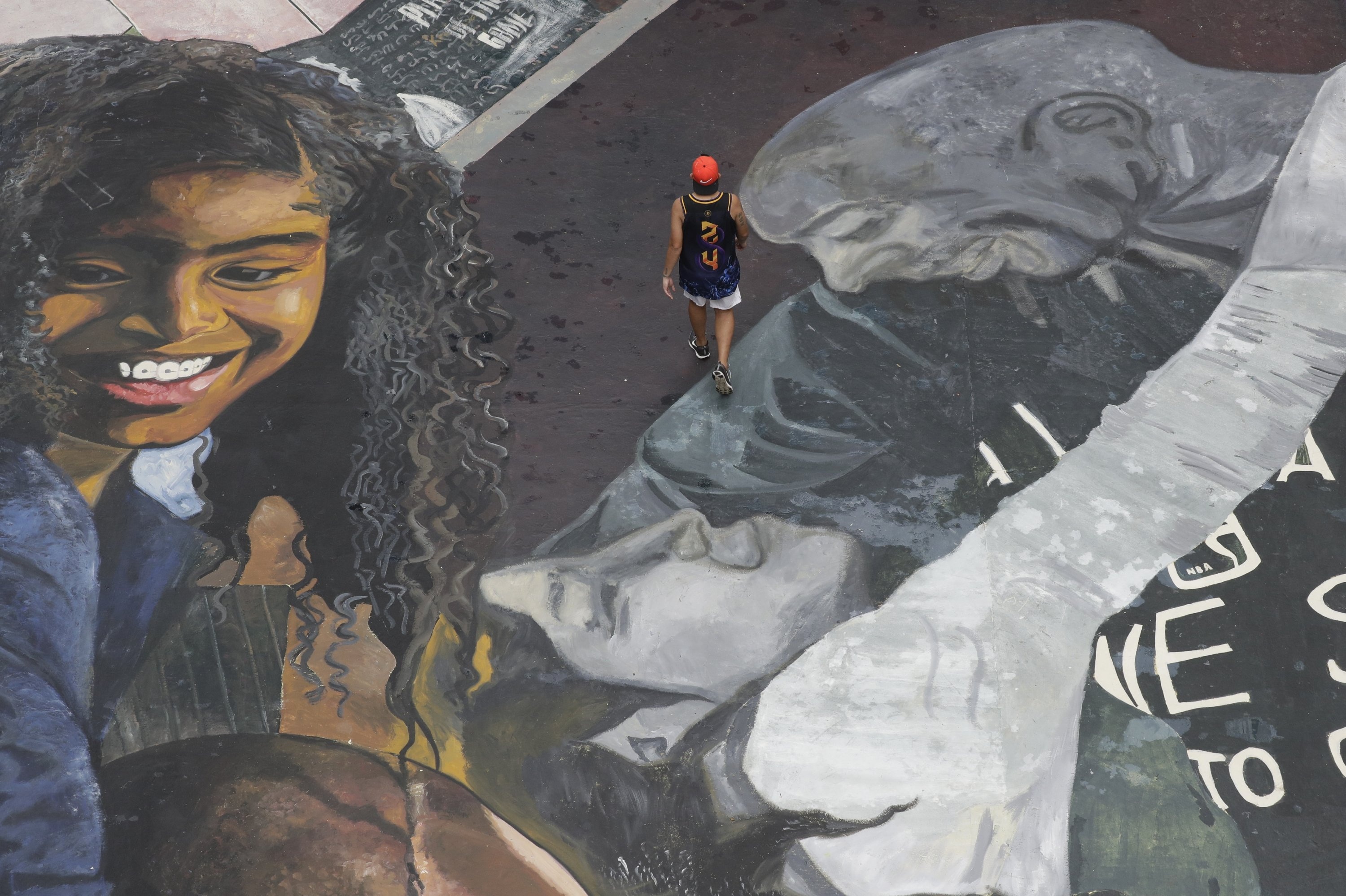 A man walks on a giant mural of former NBA basketball player Kobe Bryant and daughter Gianna on a basketball court at a tenement building in Taguig, Philippines, Jan. 26, 2021. (AP Photo)