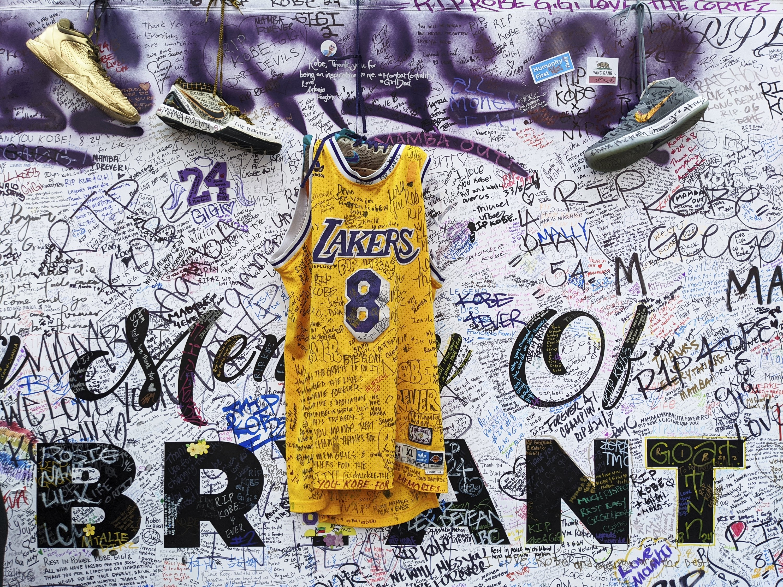 In this Feb. 2, 2020, file photo, sneakers and a Los Angeles Lakers uniform with the numbers worn by NBA star Kobe Bryant are left at a memorial for Bryant while fans gather to pay their respect near Staples Center in Los Angeles. (AP Photo)