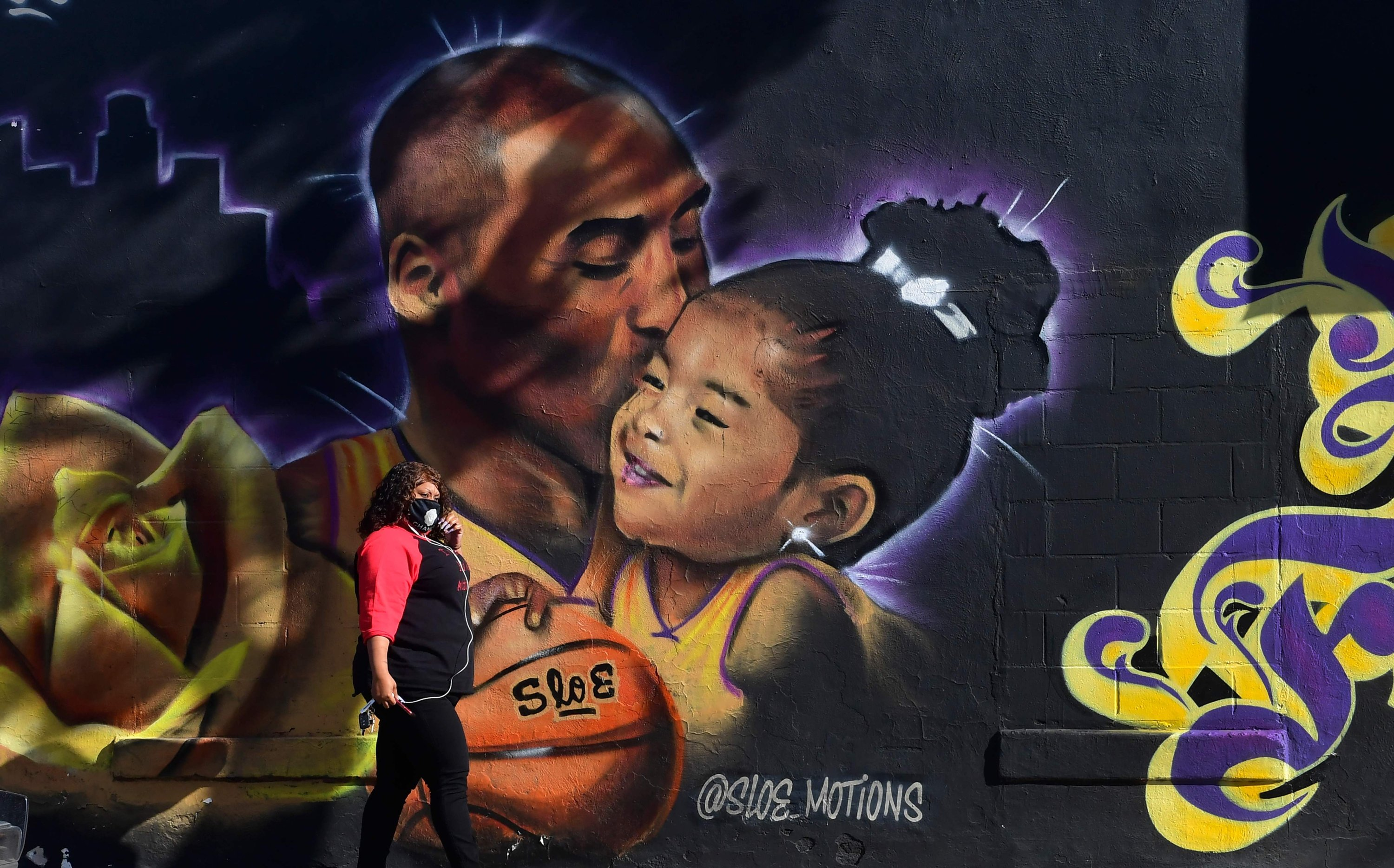 A pedestrian adjusts her facemask walking past a mural of the late Los Angeles Lakers basketball star Kobe Bryant and his daughter Gianna by artist @Sloe_Motions, Los Angeles, California, Jan. 25, 2021. (AFP Photo)