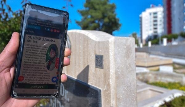 Information regarding the deceased is displayed on a cellphone screen next to a QR code on a gravestone, in Antalya, southern Turkey, Jan. 26, 2021. (DHA PHOTO)