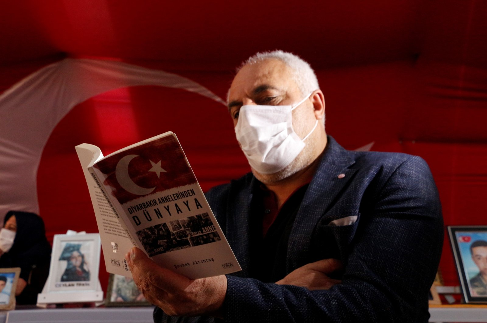 """Father Şevket Altıntaş poses with his book """"From Diyarbakır Mothers to the World"""" in front of the pro-PKK Peoples' Democratic Party's (HDP) headquarters in Diyarbakır, Turkey, Jan. 25, 2021. (DHA Photo)"""