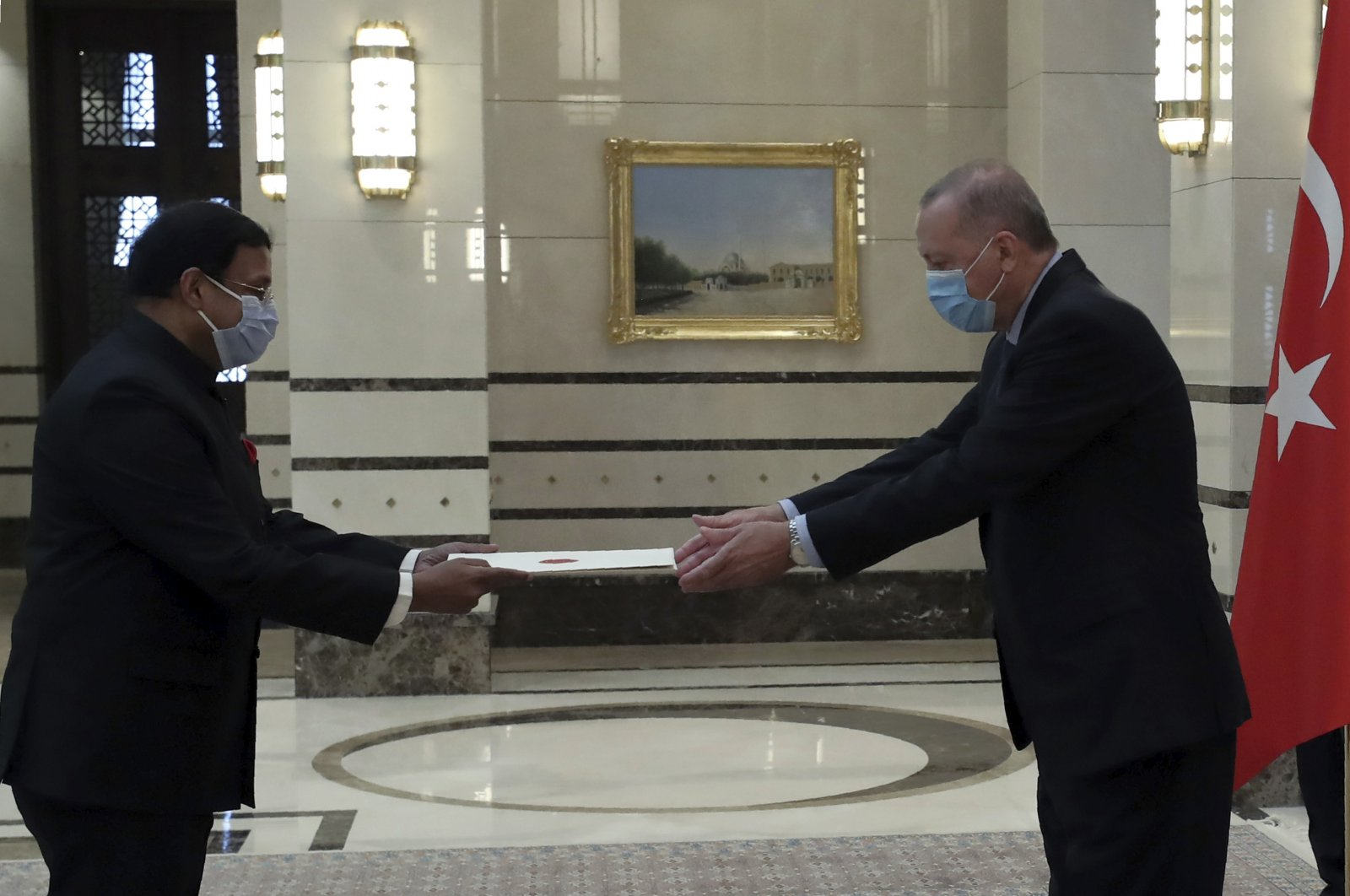Turkey's President Recep Tayyip Erdoğan, wearing a face mask to protect against the spread of coronavirus, receives a letter of credentials from the new ambassador of India, Sanjay Kumar Panda, during a ceremony at the presidential palace, in Ankara, Turkey, Wednesday, Aug. 19, 2020. (Turkish Presidency via AP, Pool)
