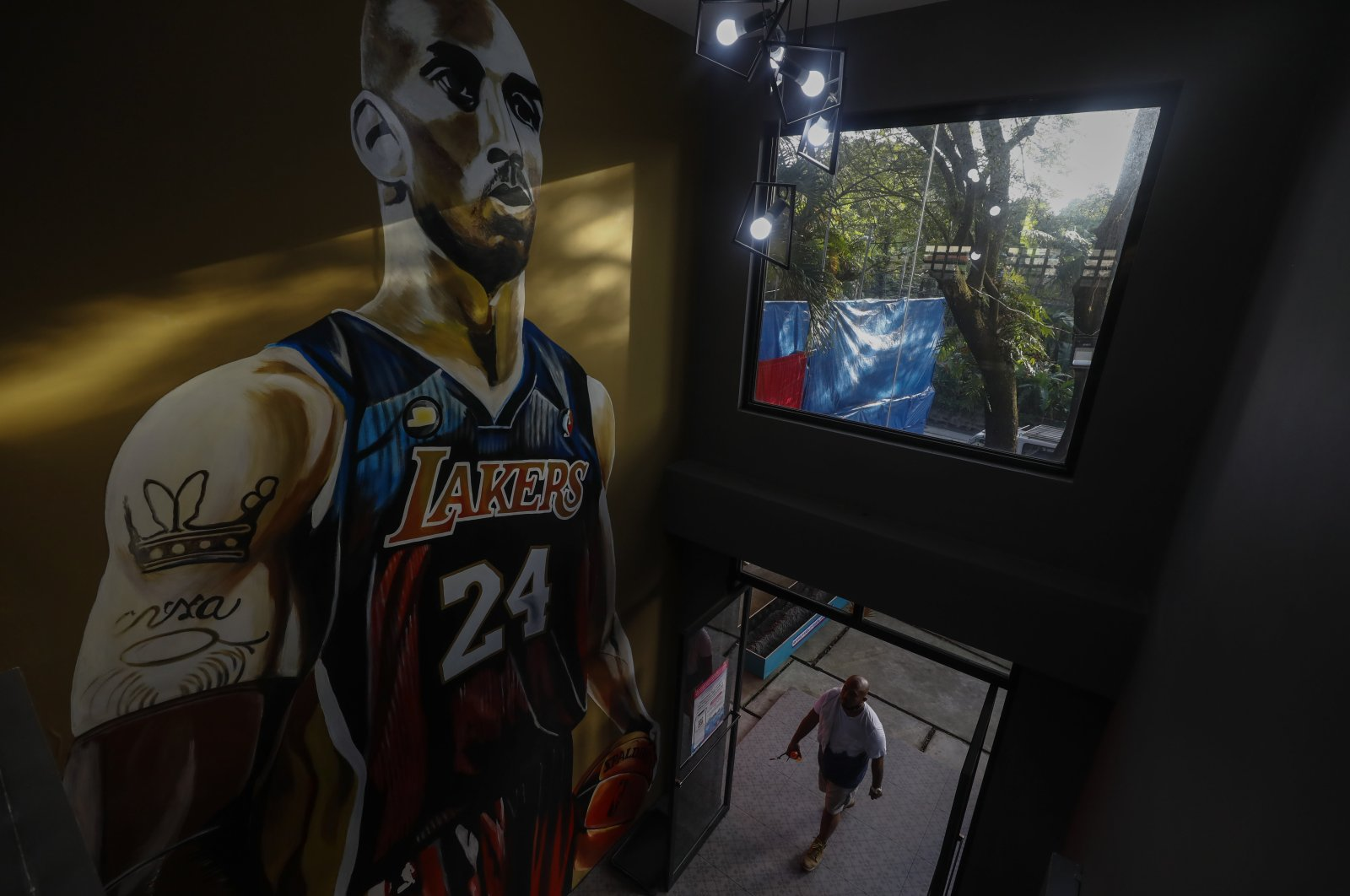 """A fan enters a basketball facility dubbed the """"House of Kobe"""" before the start of a ceremony marking the first death anniversary of the late basketball player Kobe Bryant in Valenzuela City, Metro Manila, Philippines, Jan. 26, 2021. (EPA Photo)"""