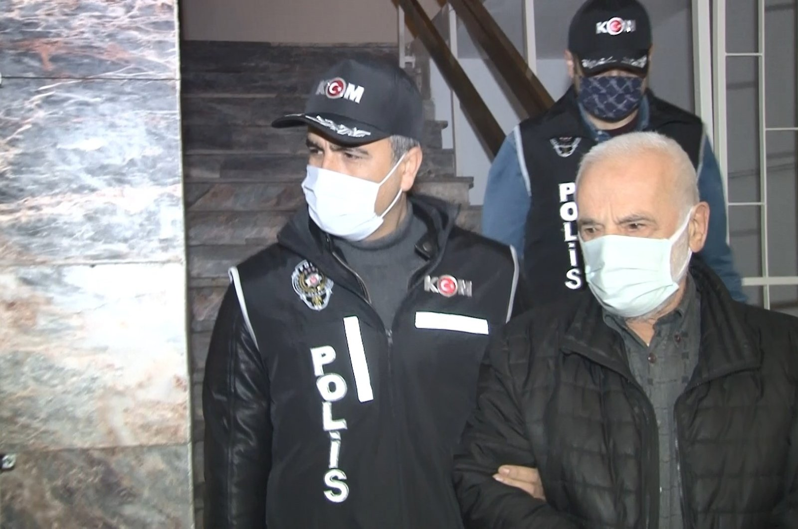 A police officer escorts a FETÖ suspect captured in Istanbul, Turkey, Jan. 26, 2021. (İHA PHOTO)