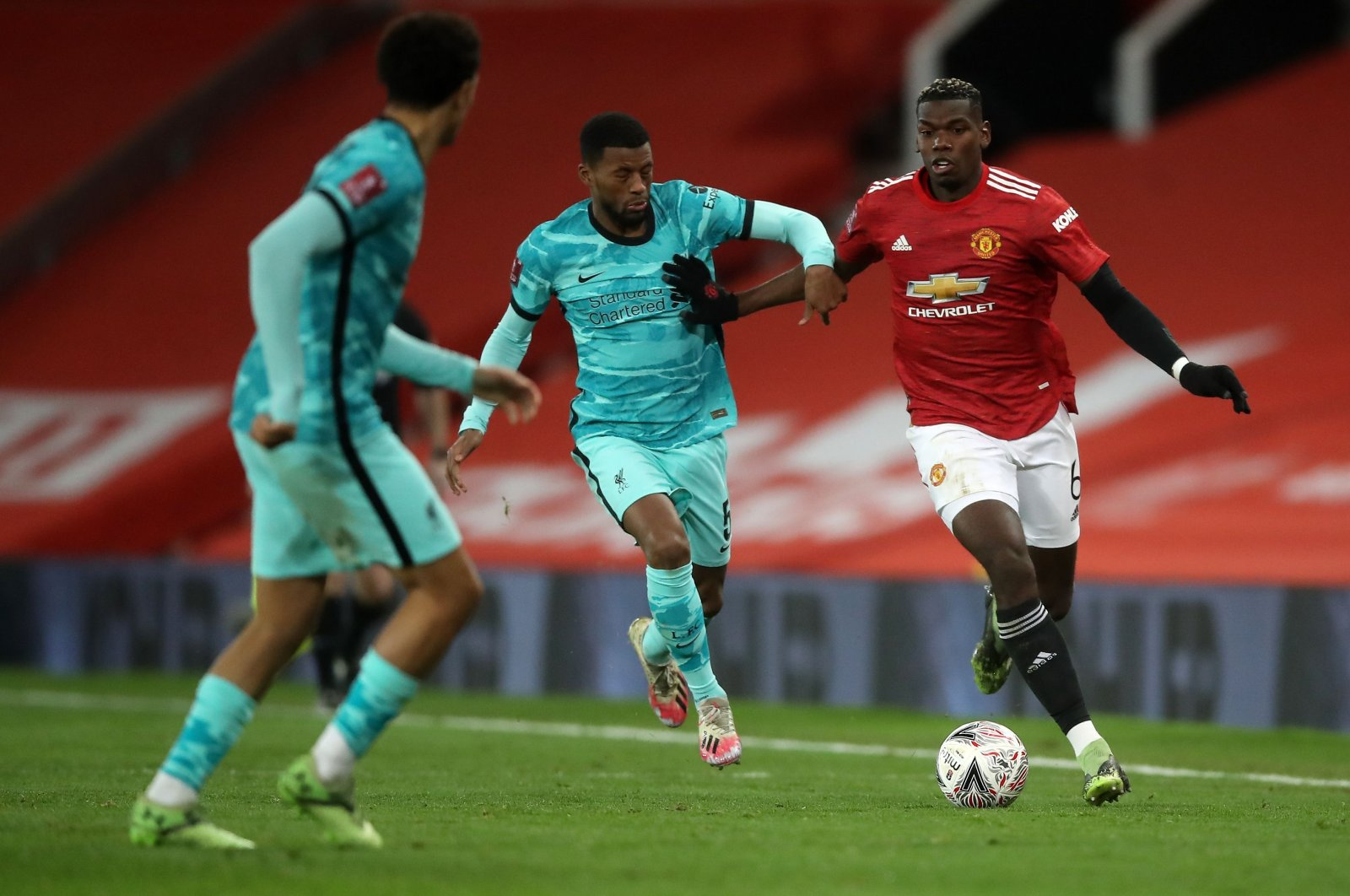 Manchester United's Paul Pogba (R) vies for the ball against Liverpool's Georginio Wijnaldum (C) during the English FA Cup fourth round match, at the Old Trafford, Manchester, England, Jan. 24, 2021.