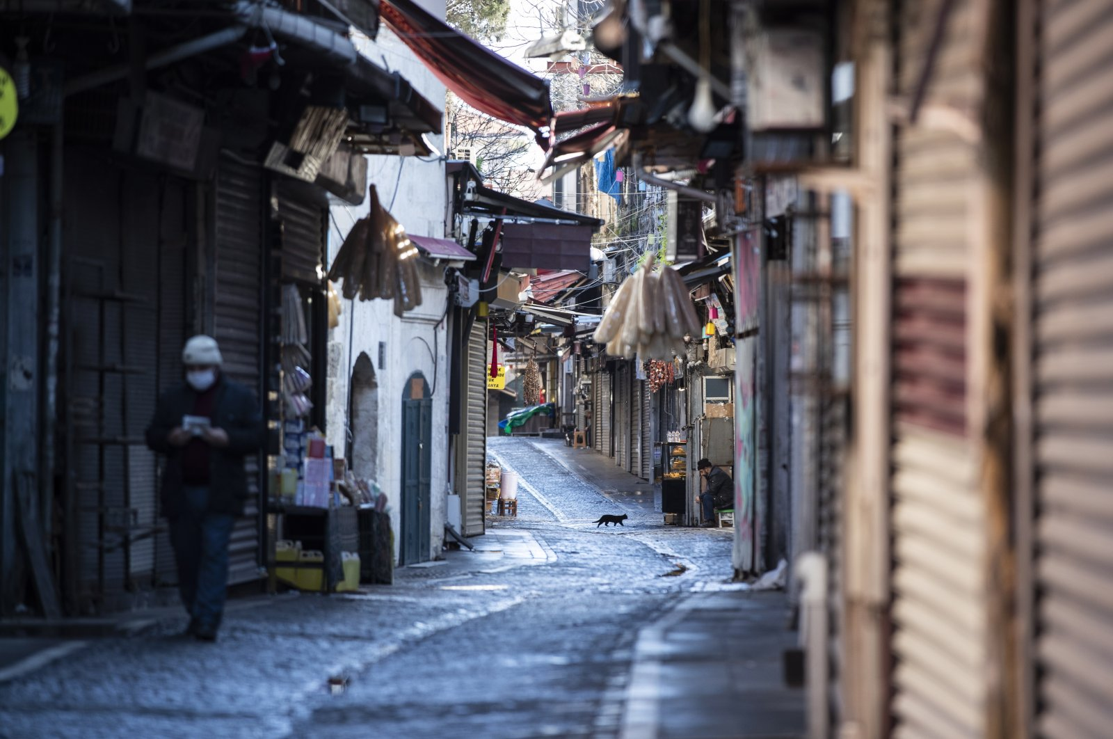 A street vendor sits near closed shops in a deserted street during the lockdown in Istanbul, Turkey, Jan. 24, 2021. (EPA Photo)