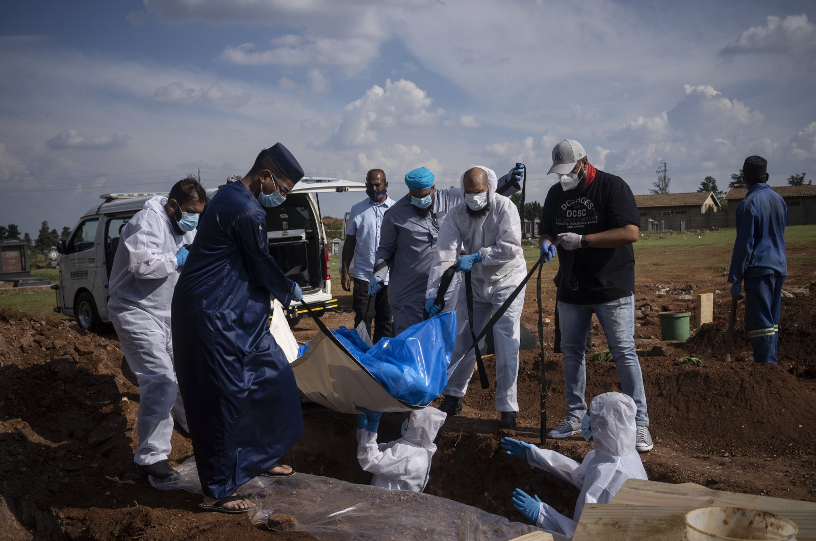 Family members and volunteers from the Saaberie Chishty Society lower the body of a COVID-19 victim into a grave at the Avalon cemetery in Lenasia, South Africa, Jan. 4, 2021. (AP Photo)