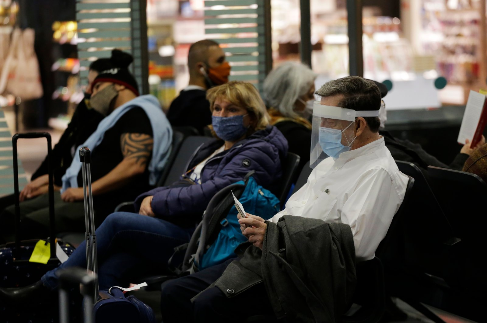 Passengers wearing face shields or masks as protection against the COVID-19 pandemic in the departure seating area of Istanbul Airport, Istanbul, Turkey, Dec. 1, 2020. (Shutterstock Photo)