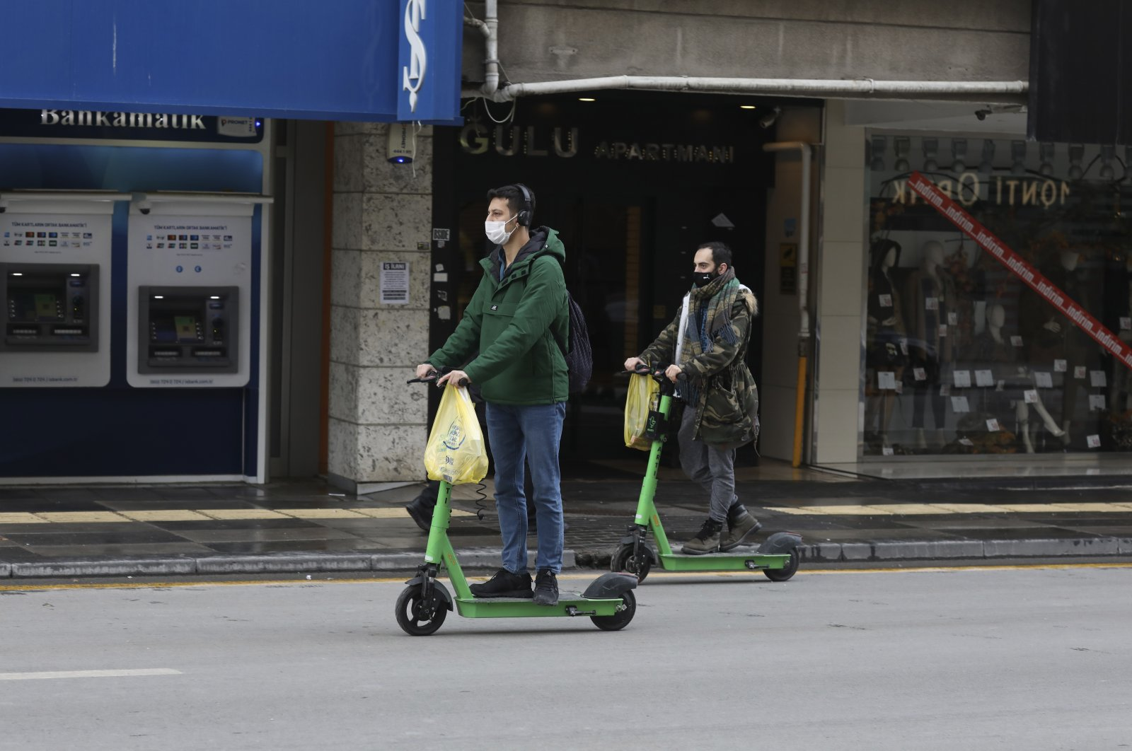 People wearing protective masks ride scooters in the capital Ankara, Turkey, Jan. 24, 2021. (AP PHOTO)