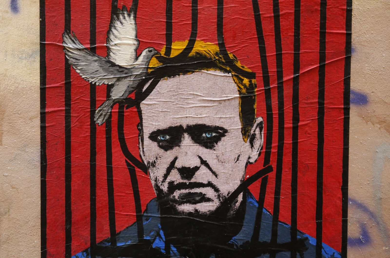A view of a large poster depicting Russian opposition leader Alexei Navalny behind bars with a dove freeing him from detention, by an unidentified street artist known as Harry Greb, in downtown Rome, Italy, Jan. 25, 2021. (EPA Photo)
