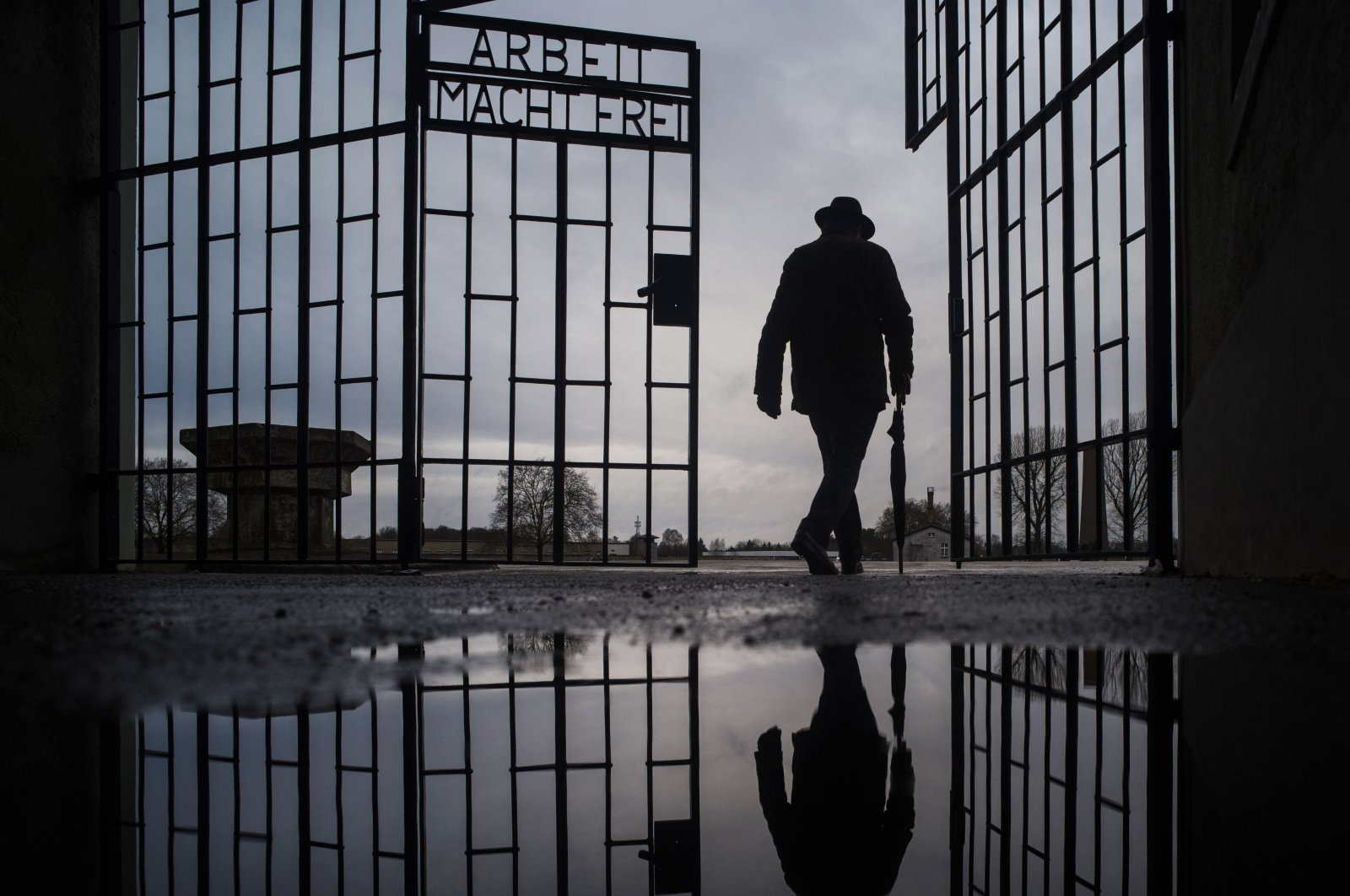 """A man walks through the gate of the Sachsenhausen Nazi death camp with the phrase ''Arbeit macht frei"""" (work sets you free) on International Holocaust Remembrance Day in Oranienburg, about 30 kilometers (18 miles) north of Berlin, Germany. Jan. 27, 2021. (AP File Photo)"""