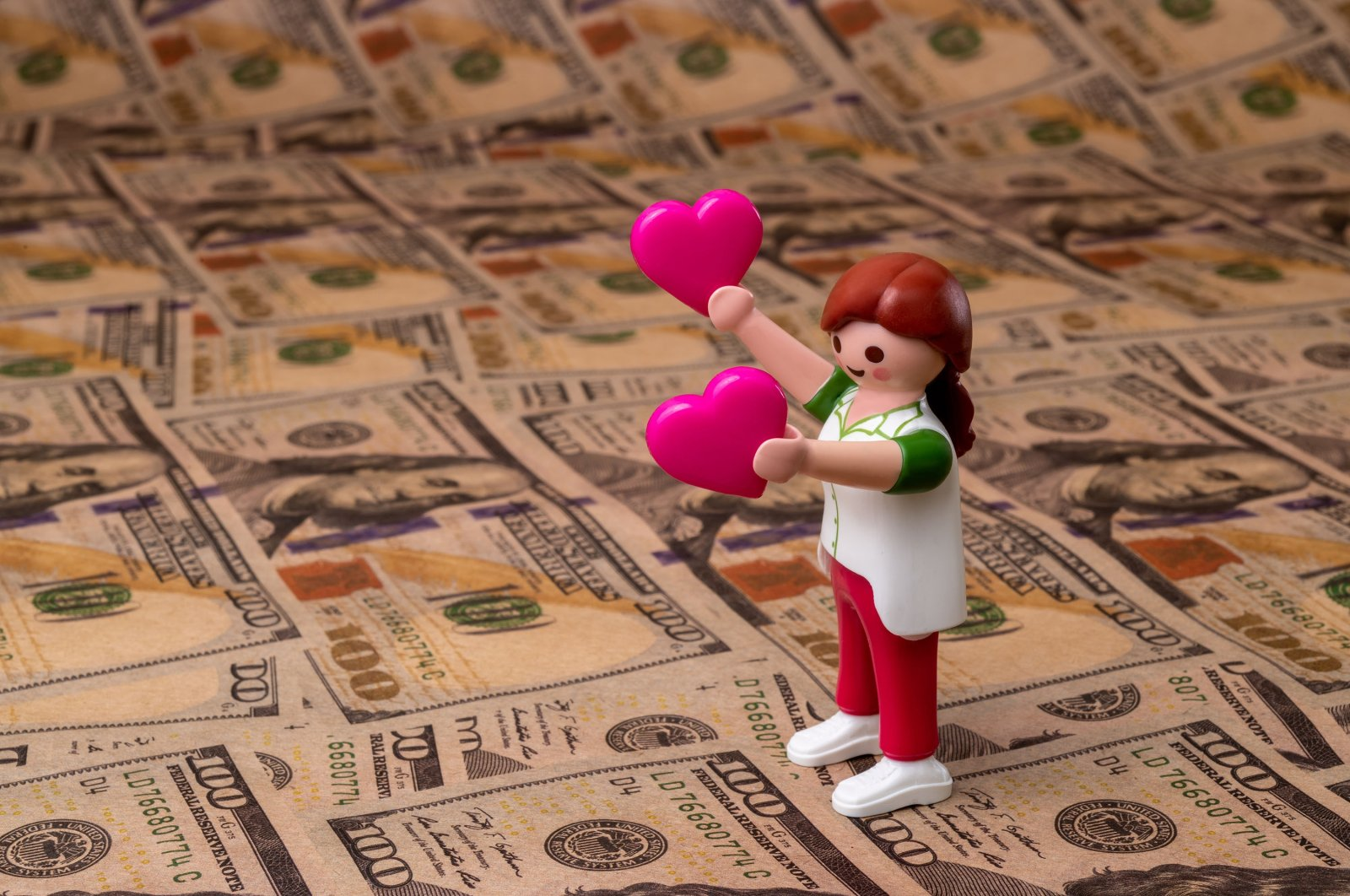 A plastic figurine of a woman holds in each hand a pink heart symbol against a background of American dollar bills. (Shutterstock Photo)