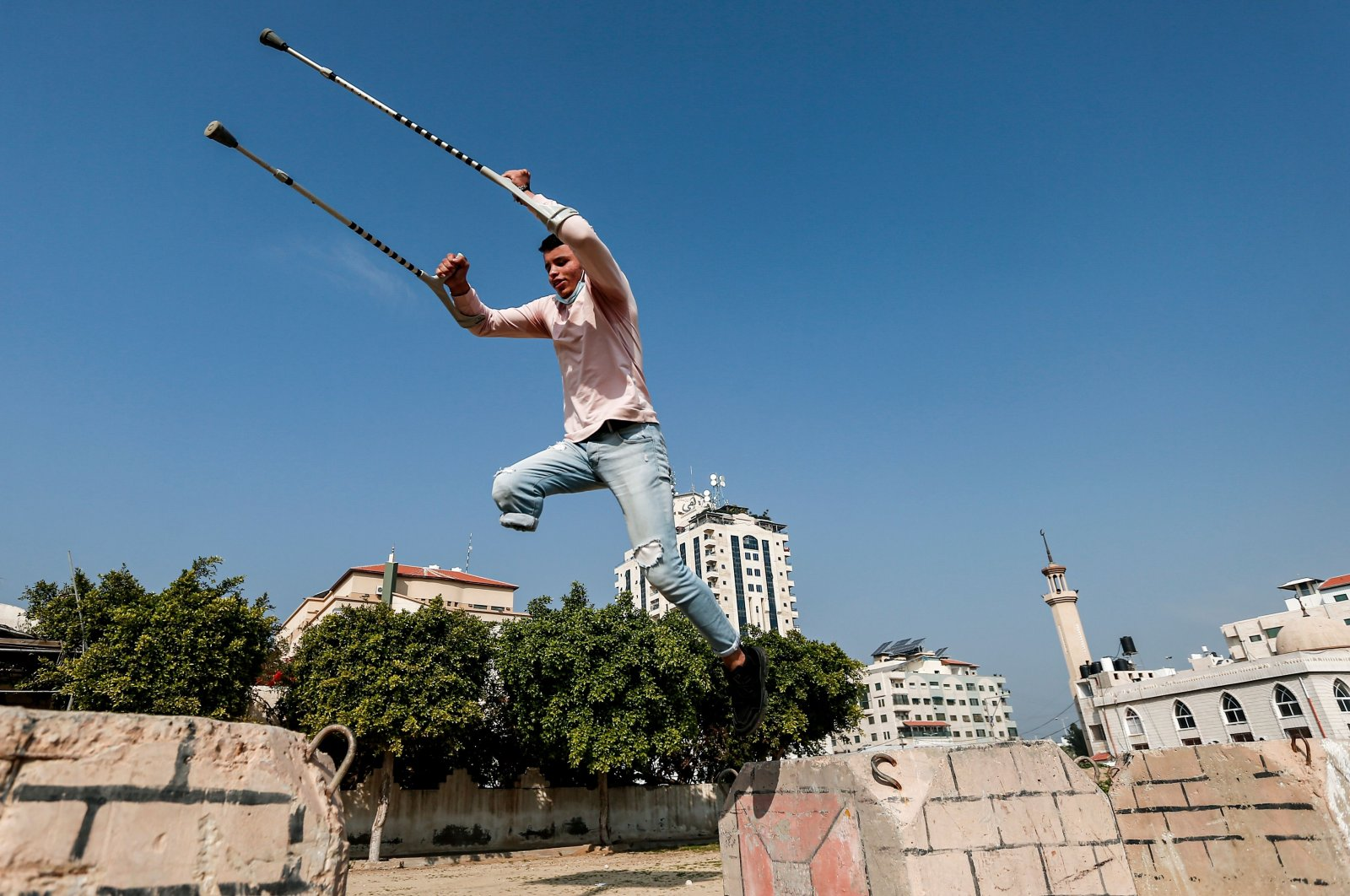 Mohamed Aliwa, a Palestinian youth whose leg was amputated near the knee in 2018 after he was hit by Israeli army fire during protests along the fortified border separating the Gaza Strip from Israel, shows off his parkour skills despite his disability and while on crutches in Gaza City, Jan. 4, 2021. (AFP Photo)